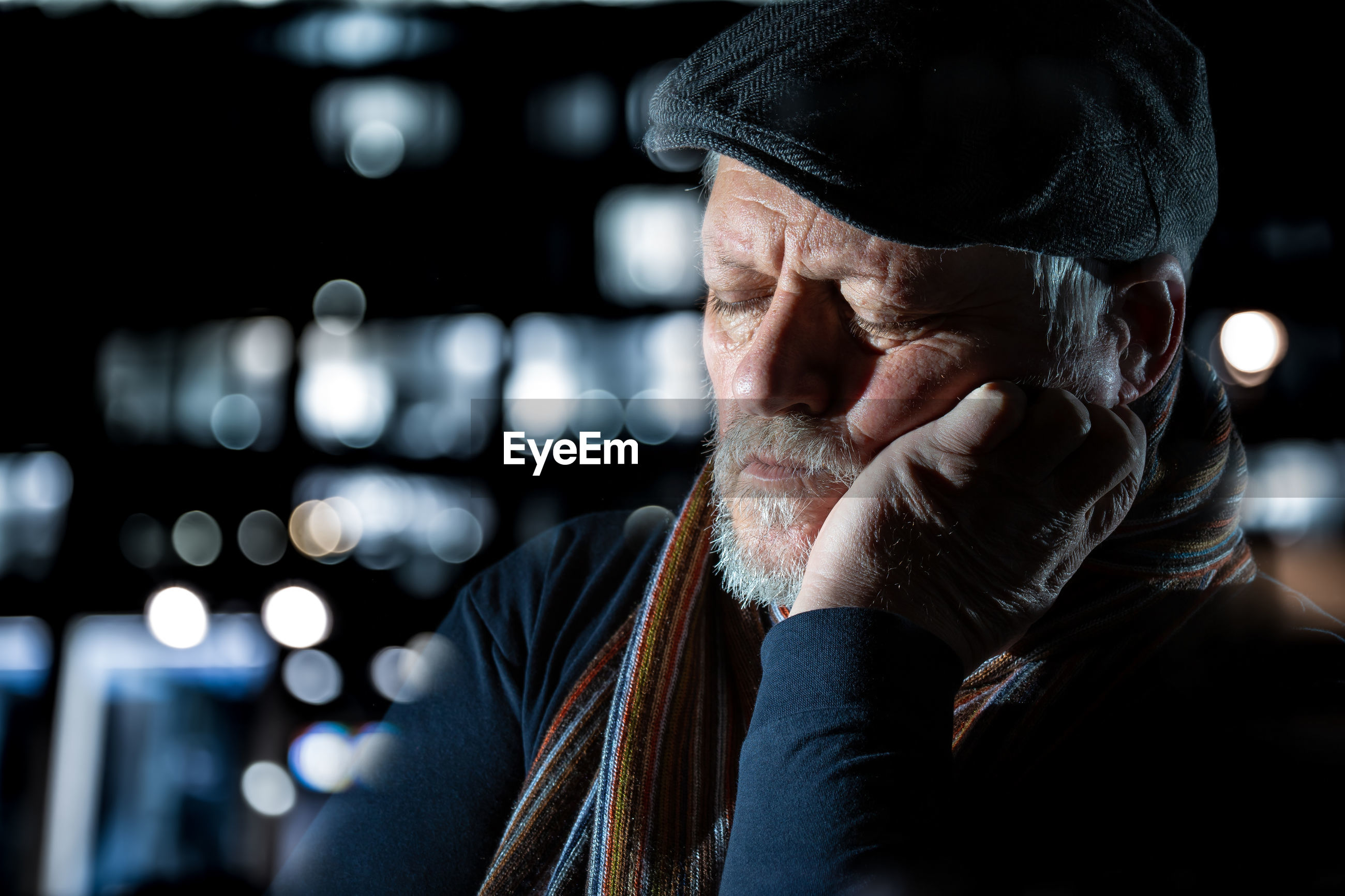 An older man is sitting outside at night. he is tired, rests his head on one hand and sleeps.