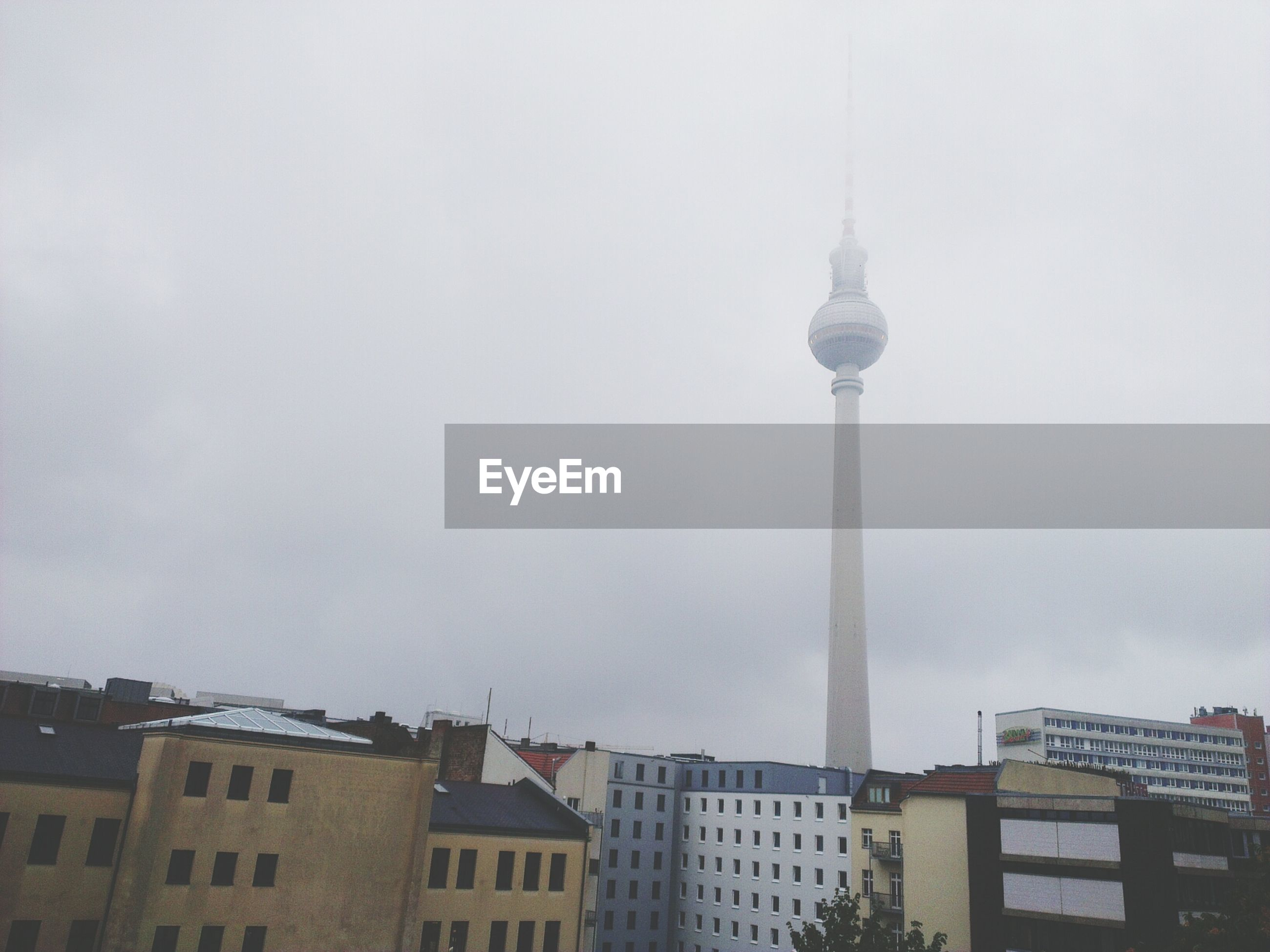 Low angle view of fernsehturm in foggy weather