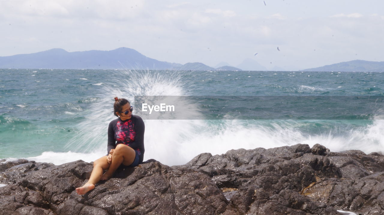 FULL LENGTH OF YOUNG WOMAN ON ROCK AT BEACH