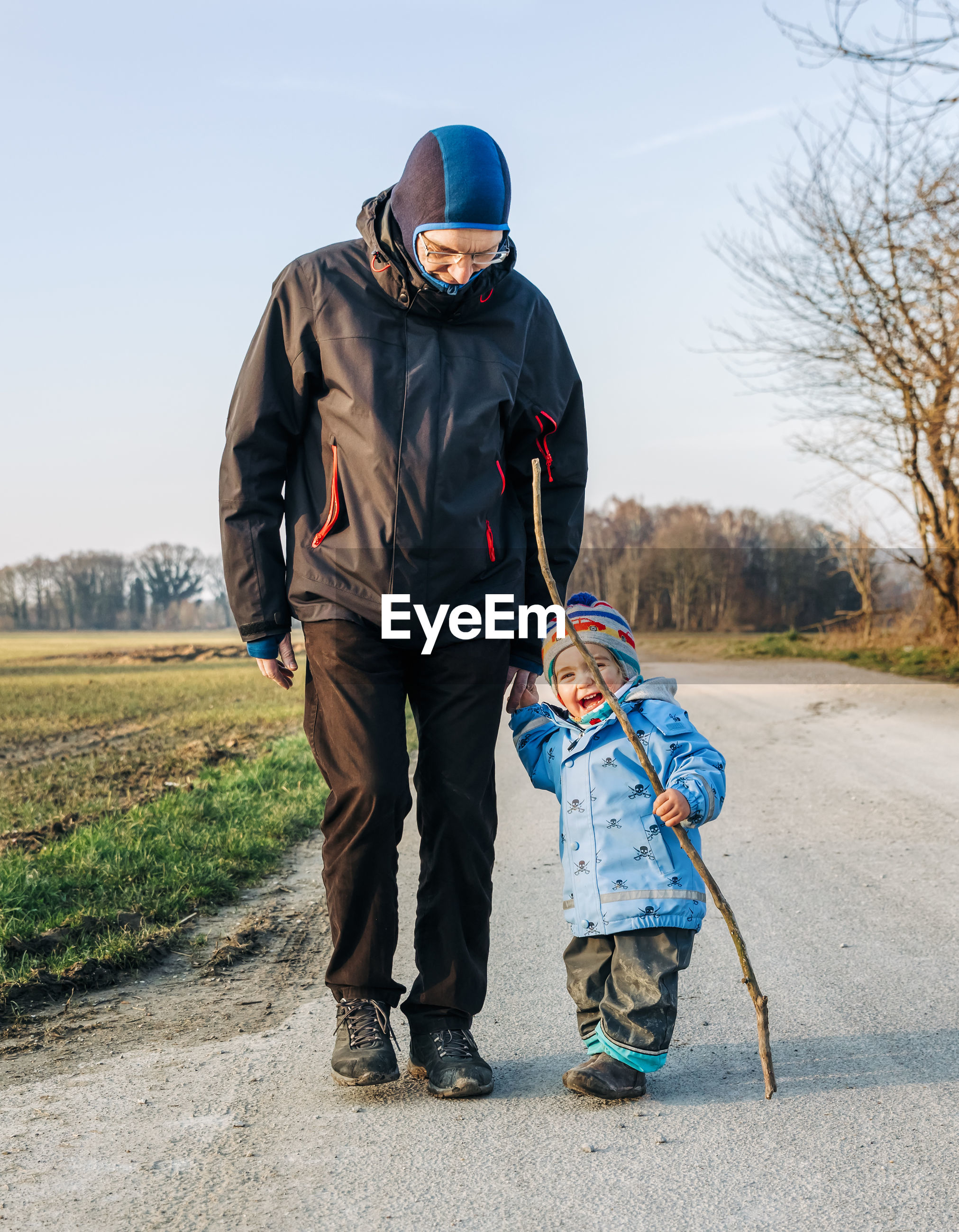 Grandfather and granddaughter walking on dirt road during winter