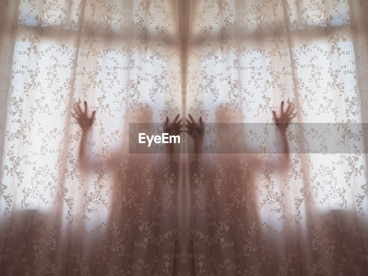 Twins Standing Behind Window Curtains At Home