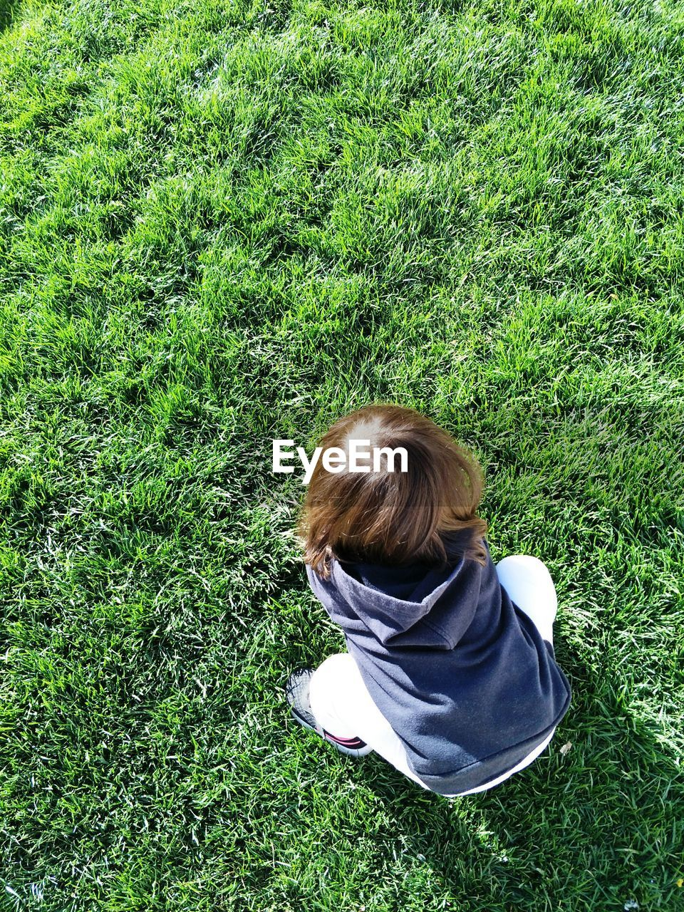 grass, green color, plant, rear view, real people, land, high angle view, leisure activity, field, one person, lifestyles, nature, growth, child, day, childhood, casual clothing, hair, relaxation, outdoors, hairstyle