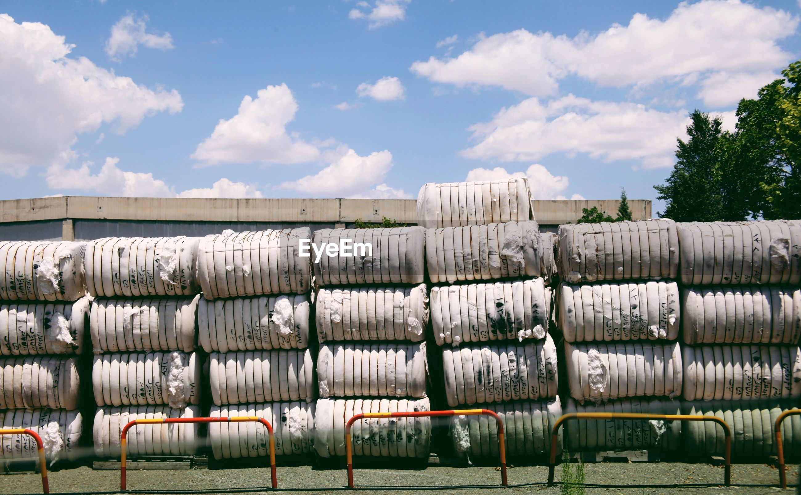Stacked cotton in fabric containers at factory against sky