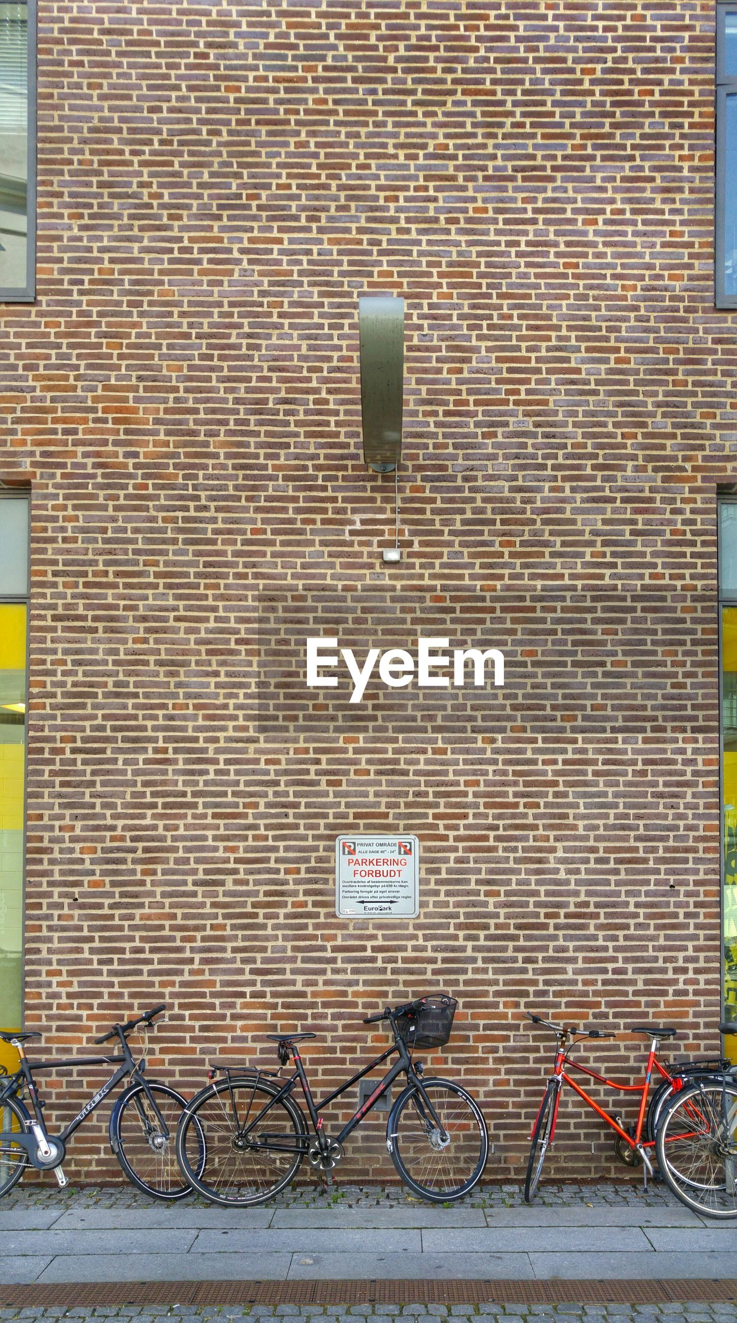 Bicycles parked by brick wall