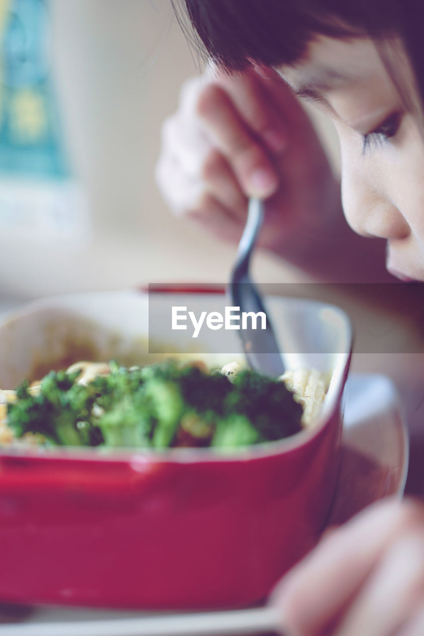 Close-Up Of Girl Eating Food From Container At Home