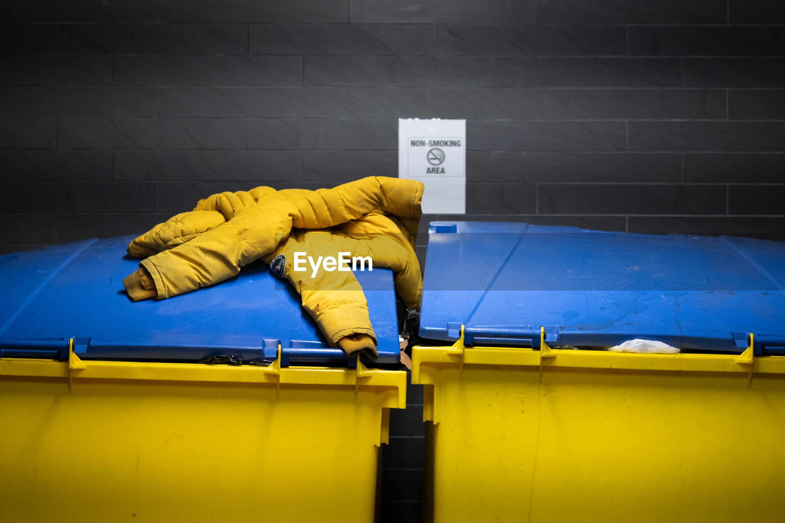 PERSON WORKING AGAINST YELLOW WALL