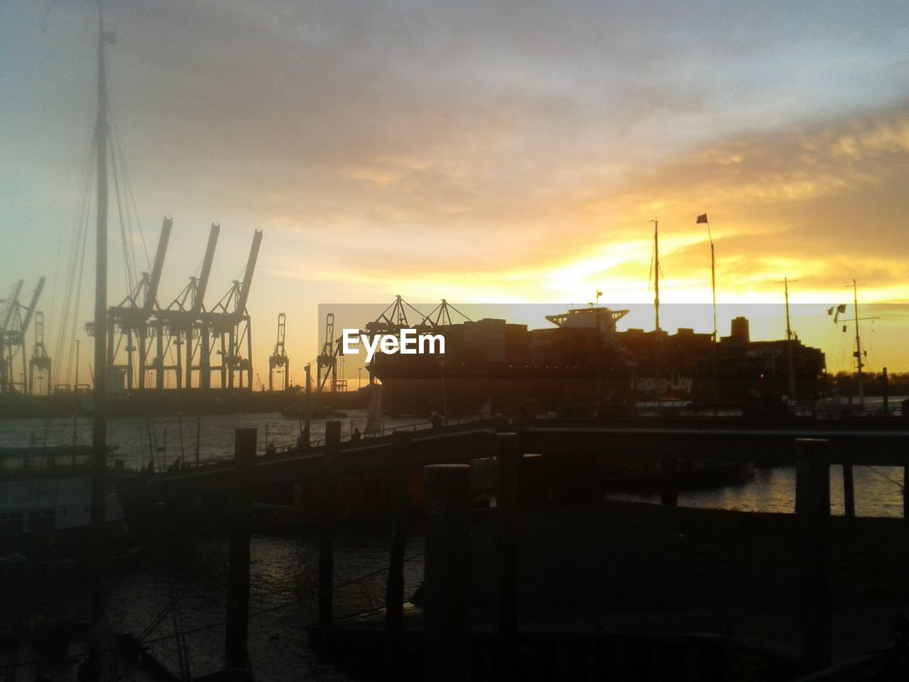 sunset, nautical vessel, harbor, commercial dock, water, sky, crane - construction machinery, transportation, pier, mode of transport, freight transportation, built structure, no people, shipping, outdoors, moored, sea, crane, industry, jetty, waterfront, cloud - sky, silhouette, shipyard, building exterior, architecture, nature, mast, city, day