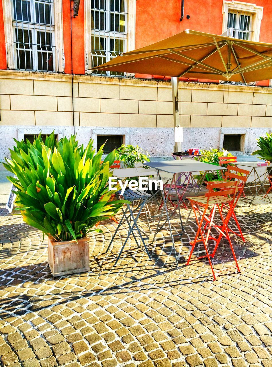 table, building exterior, chair, outdoors, architecture, day, sidewalk cafe, no people, built structure, food