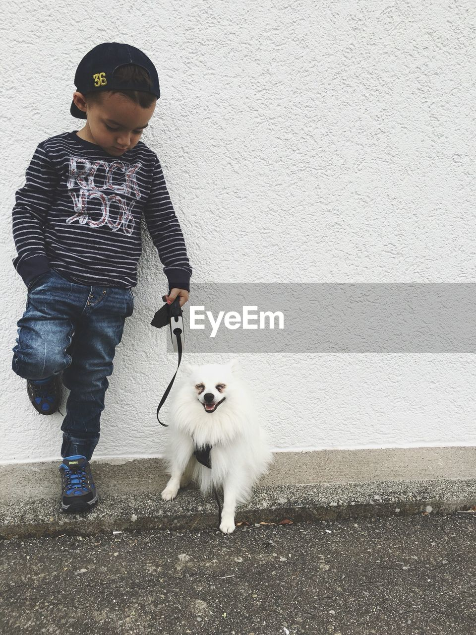 Fashionable Boy Standing By Pomeranian Against White Wall
