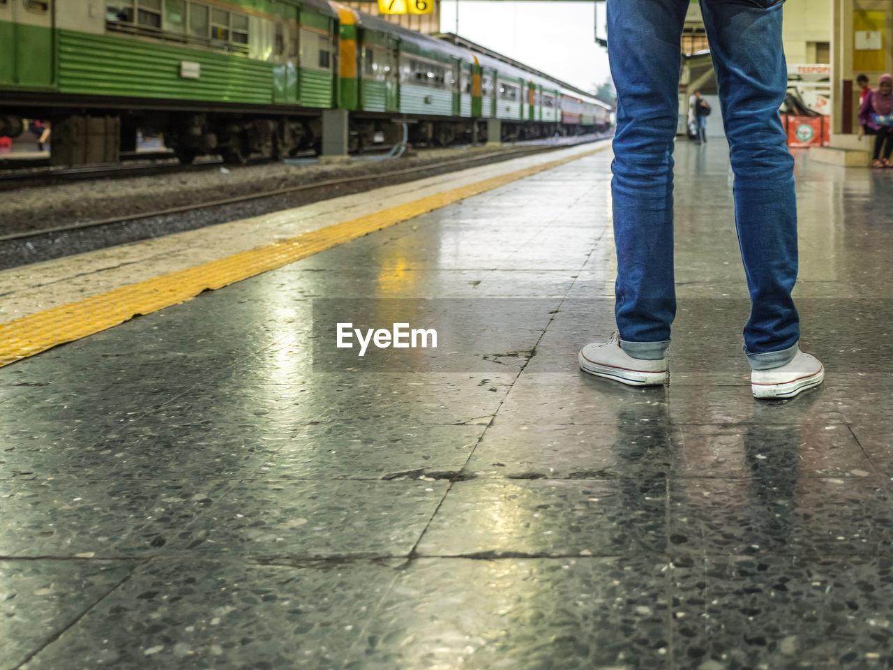low section, transportation, rail transportation, real people, wet, one person, track, human leg, human body part, mode of transportation, railroad track, shoe, body part, casual clothing, day, standing, jeans, rain, outdoors, rainy season