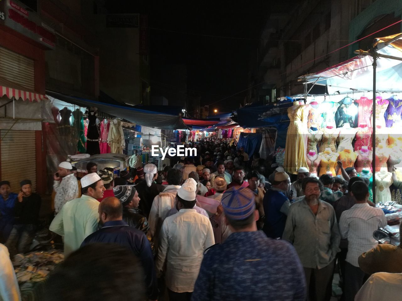 group of people, market, real people, city, large group of people, crowd, men, retail, architecture, street, women, market stall, adult, built structure, illuminated, night, lifestyles, shopping, business, street market, consumerism