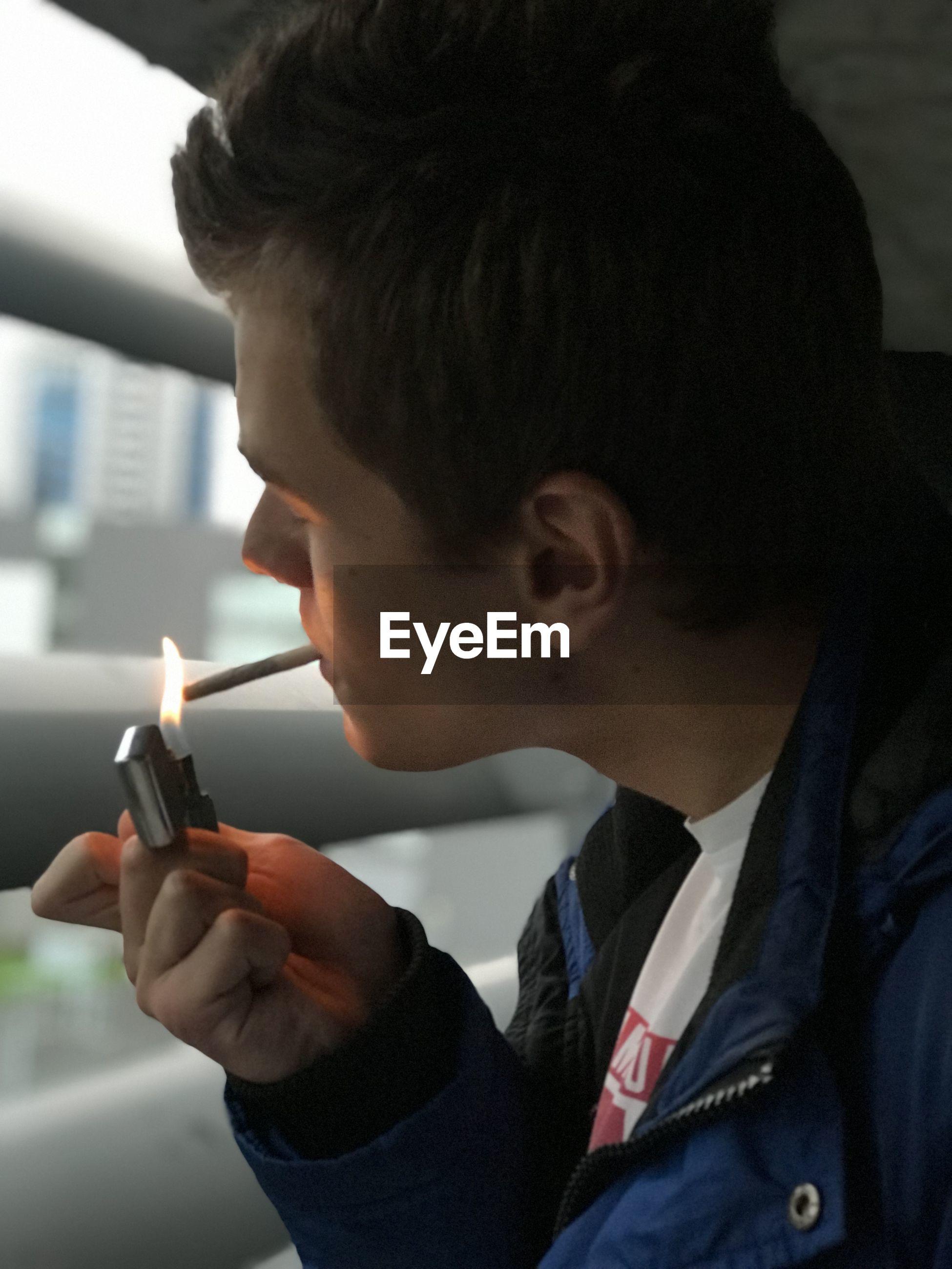 Close-up of man lighting marijuana joint