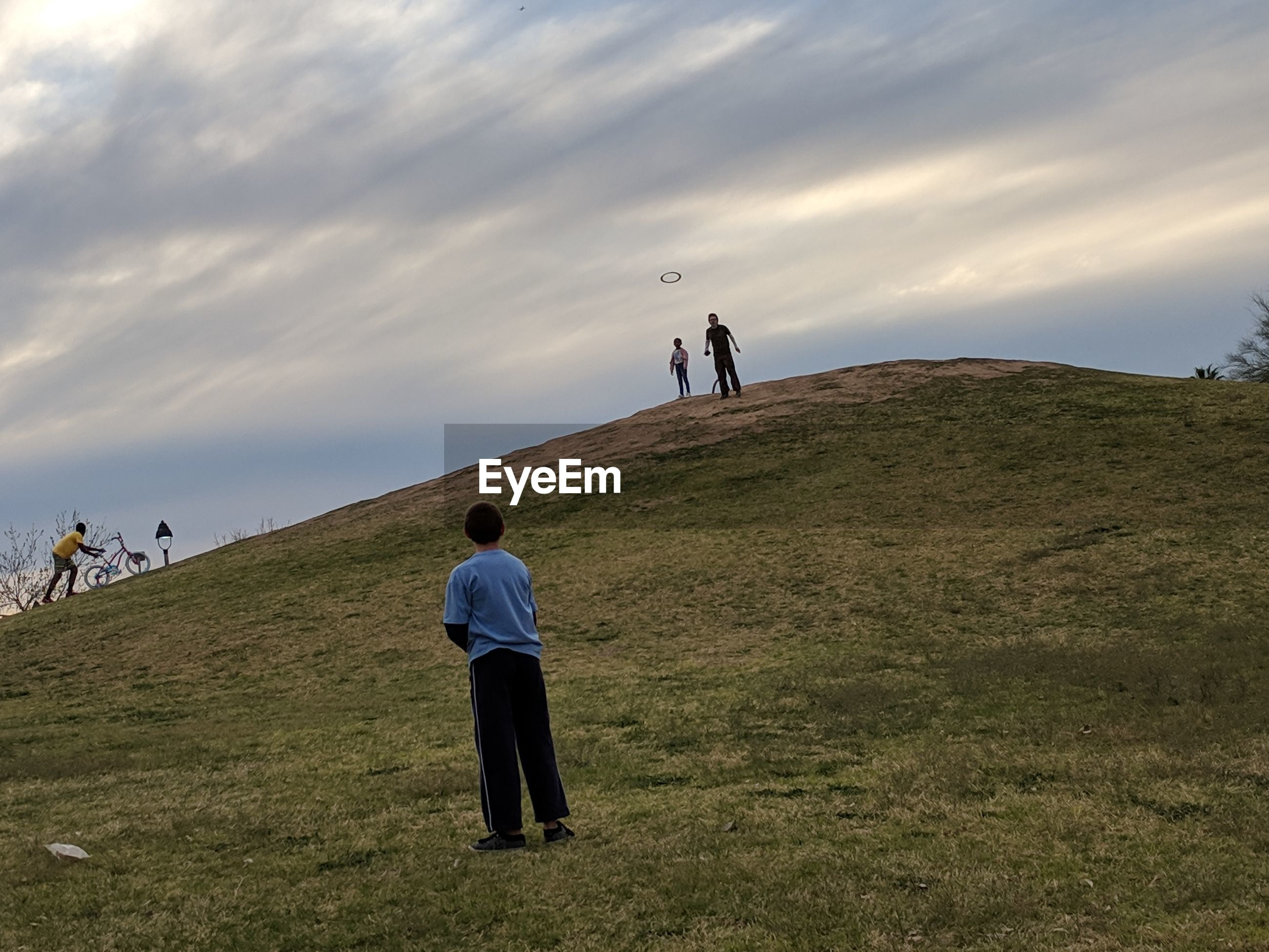 Friends playing on hill against cloudy sky