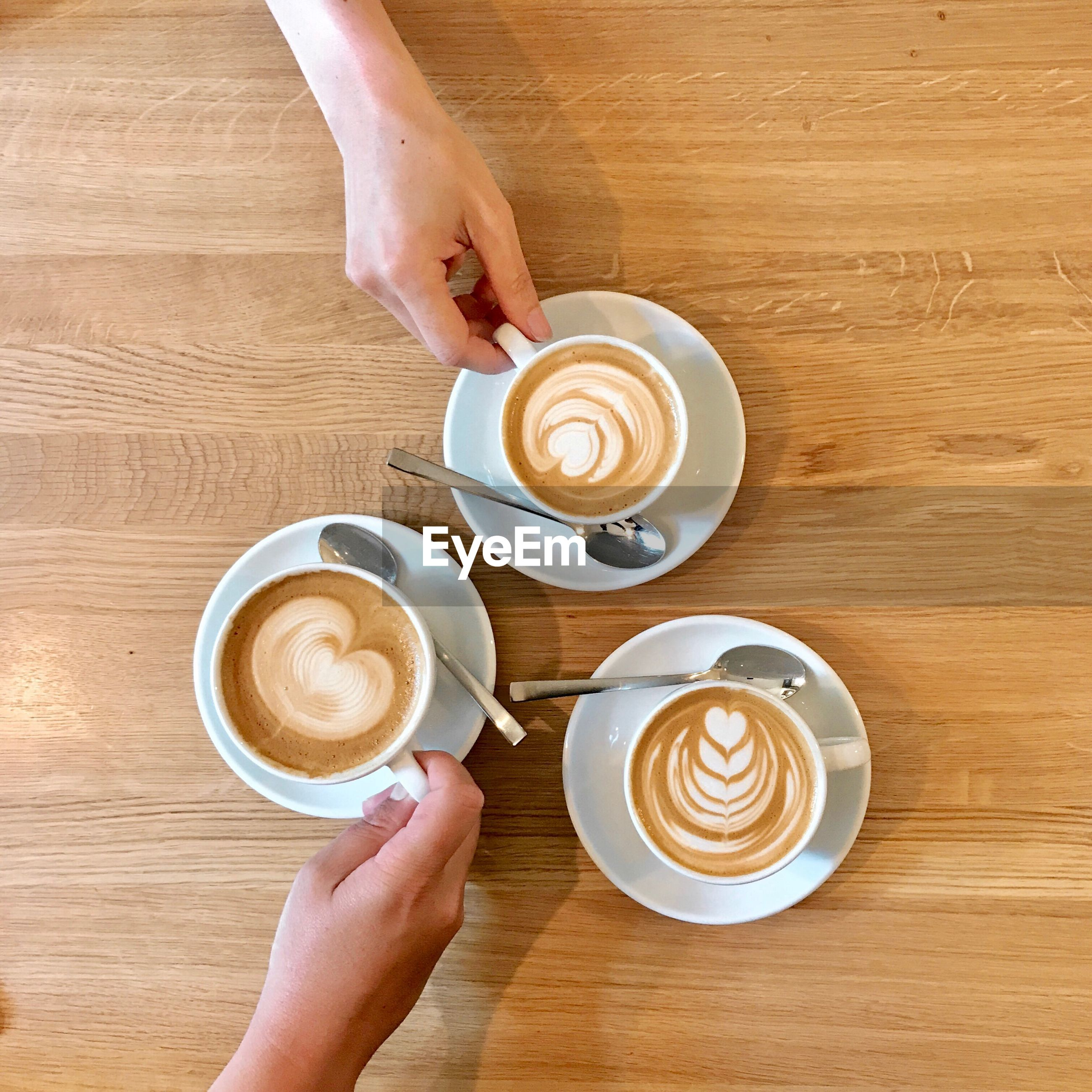Cropped hands of people having cappuccino on table