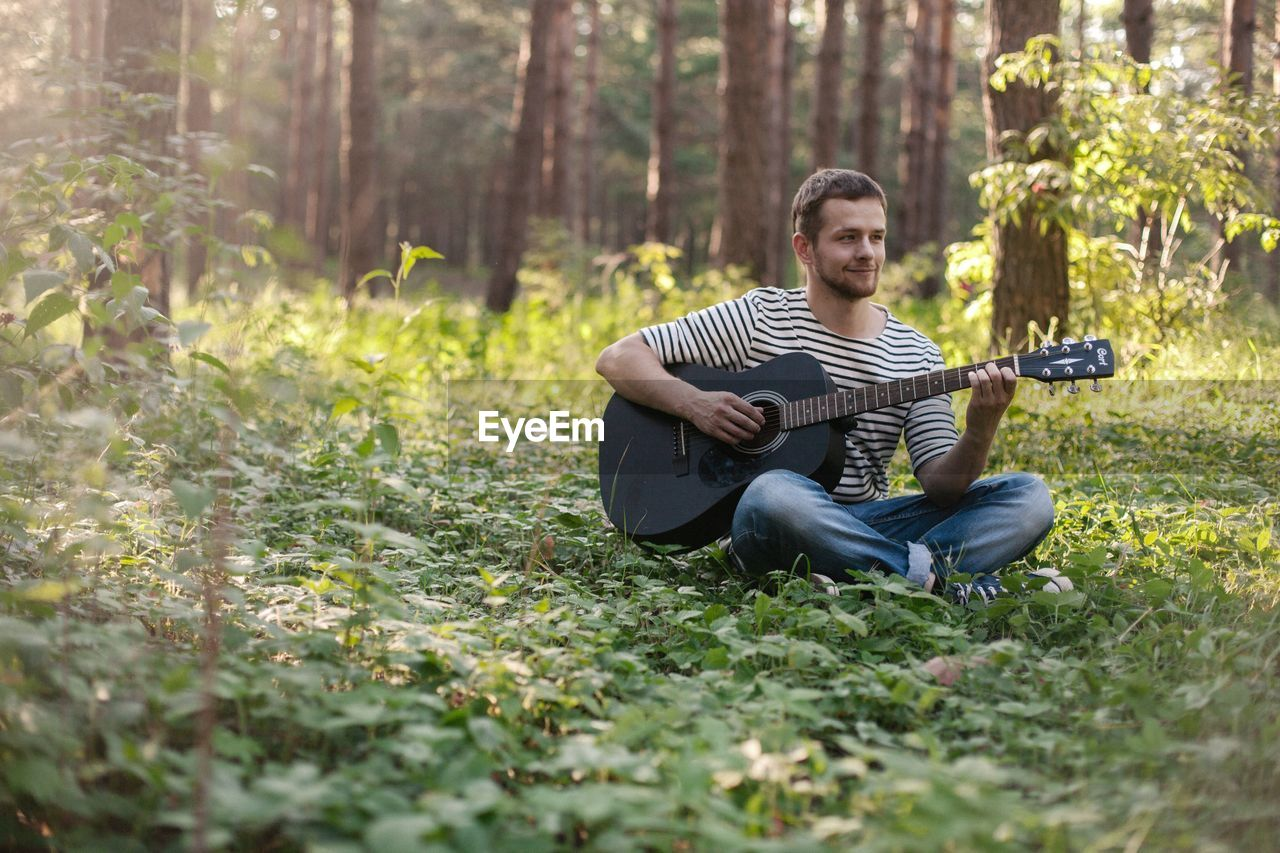 Young man playing guitar while sitting in forest