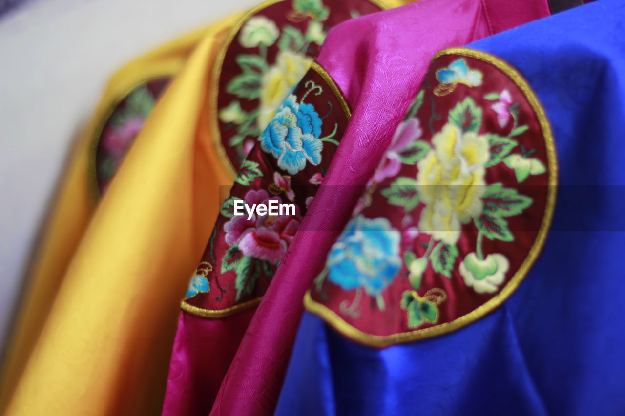 close-up, multi colored, selective focus, indoors, no people, choice, variation, blue, textile, still life, yellow, art and craft, clothing, pattern, focus on foreground, day, pink color, retail, for sale, high angle view, floral pattern, purple
