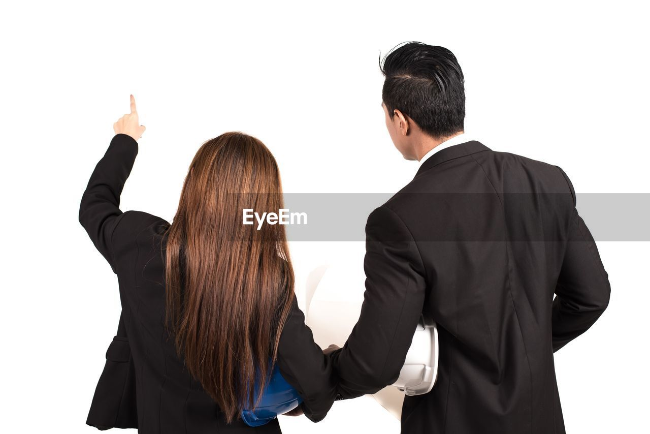 Rear view of business people discussing against white background