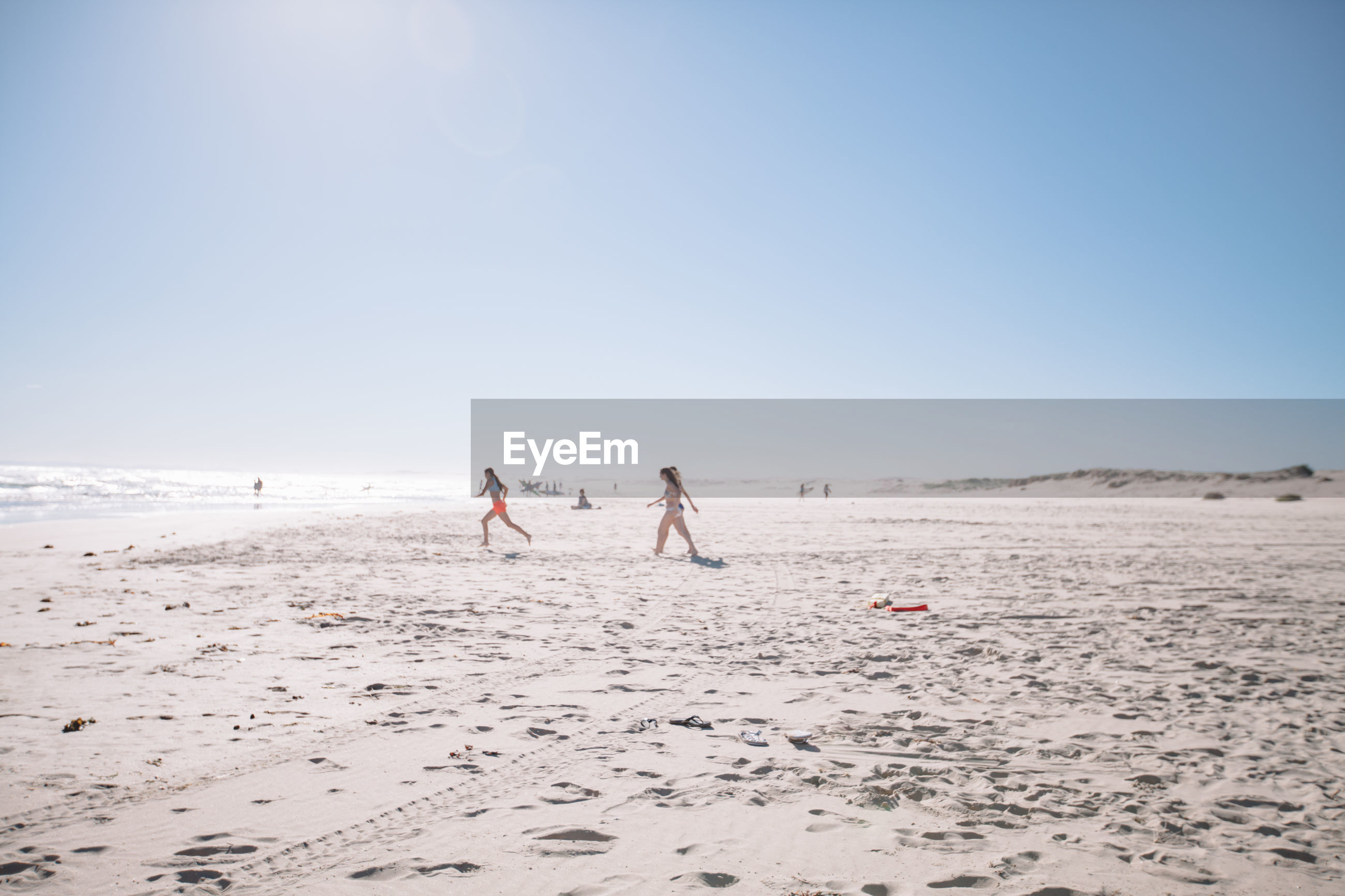 PEOPLE PLAYING ON BEACH AGAINST SKY