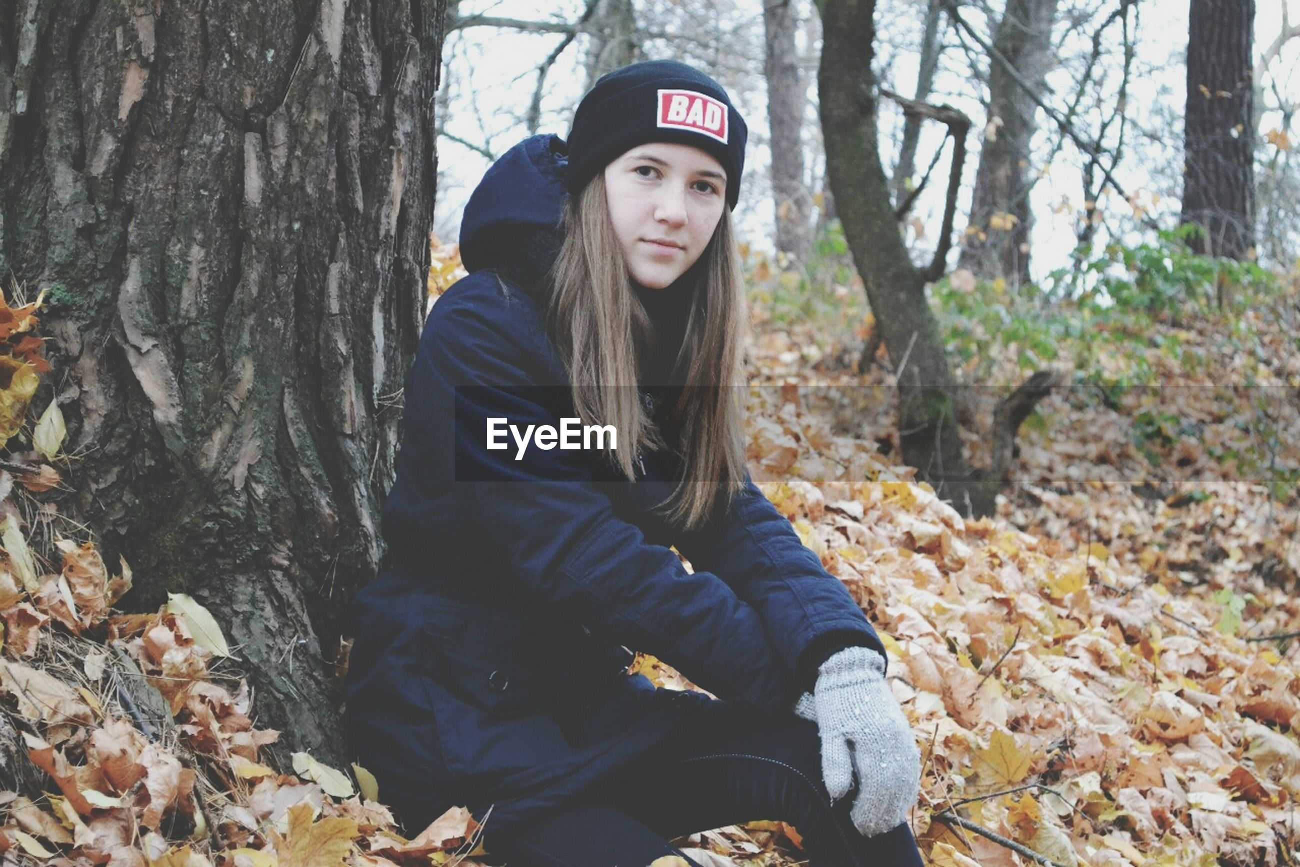 young adult, portrait, looking at camera, tree, lifestyles, casual clothing, person, front view, leisure activity, forest, standing, young women, tree trunk, smiling, three quarter length, warm clothing, day