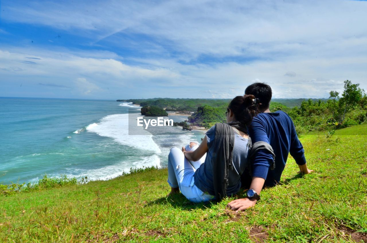 rear view, water, sky, sea, land, beauty in nature, real people, two people, sitting, scenics - nature, women, leisure activity, nature, people, casual clothing, togetherness, beach, horizon, couple - relationship, positive emotion, horizon over water, outdoors, arm around, looking at view