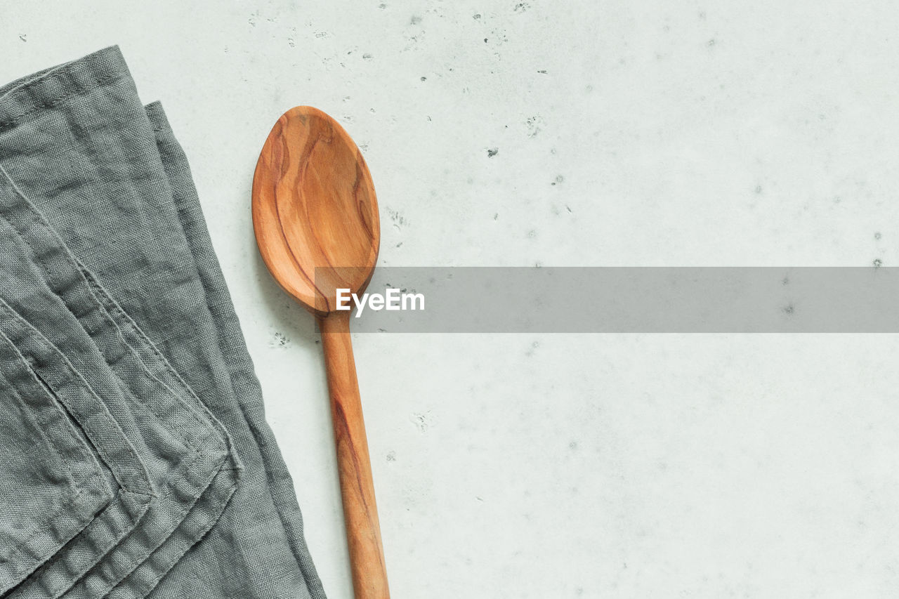 Directly above shot of wooden spoon and napkin on table