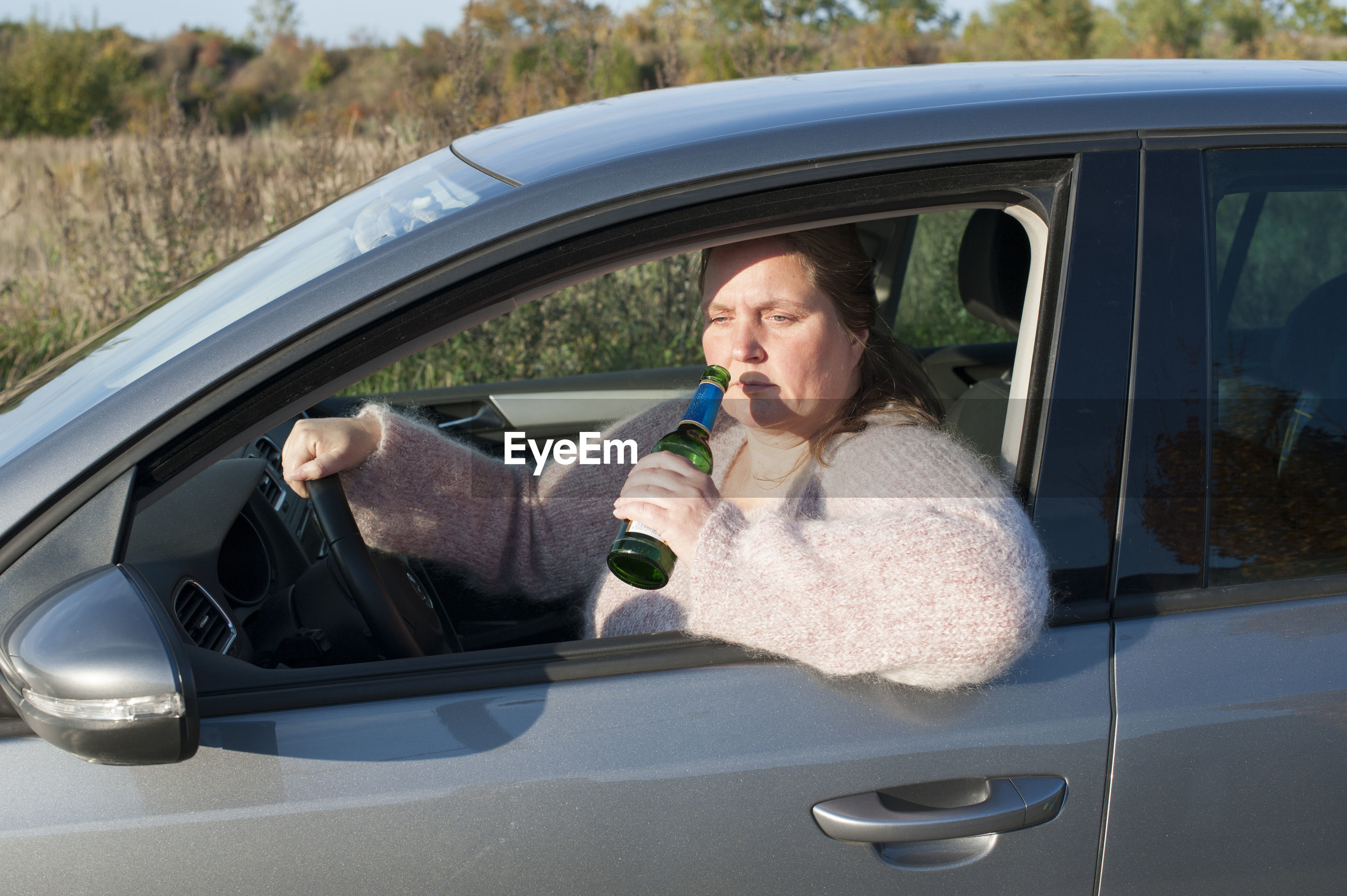 Woman drinking beer from bottle while sitting in car