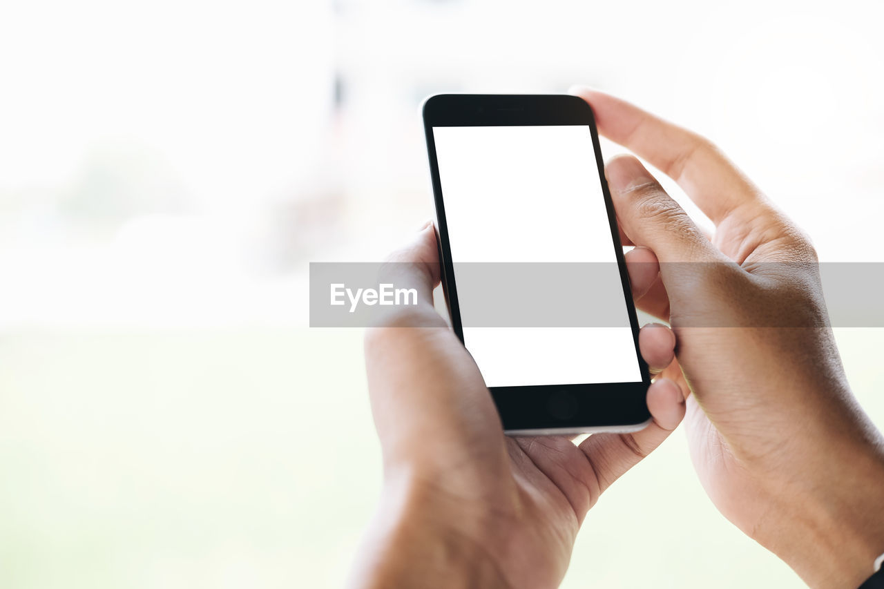 Cropped hands of person using mobile phone