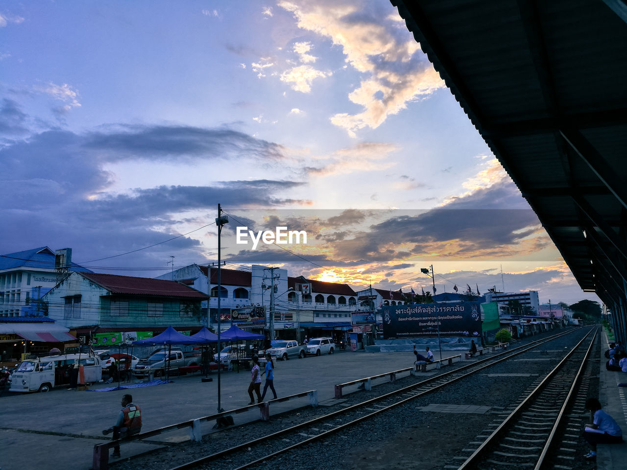 built structure, transportation, sky, architecture, building exterior, cloud - sky, railroad track, rail transportation, large group of people, real people, outdoors, public transportation, sunset, day, lifestyles, men, city, people