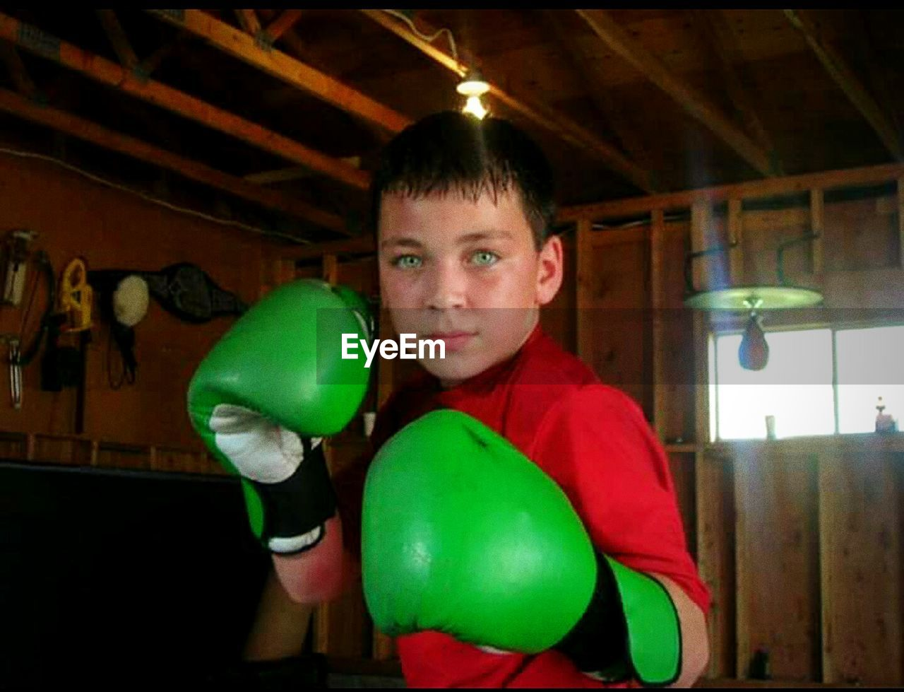 looking at camera, portrait, one person, indoors, real people, young adult, front view, green color, casual clothing, standing, holding, lifestyles, leisure activity, young men, childhood, boxing glove, boys, happiness, day, people