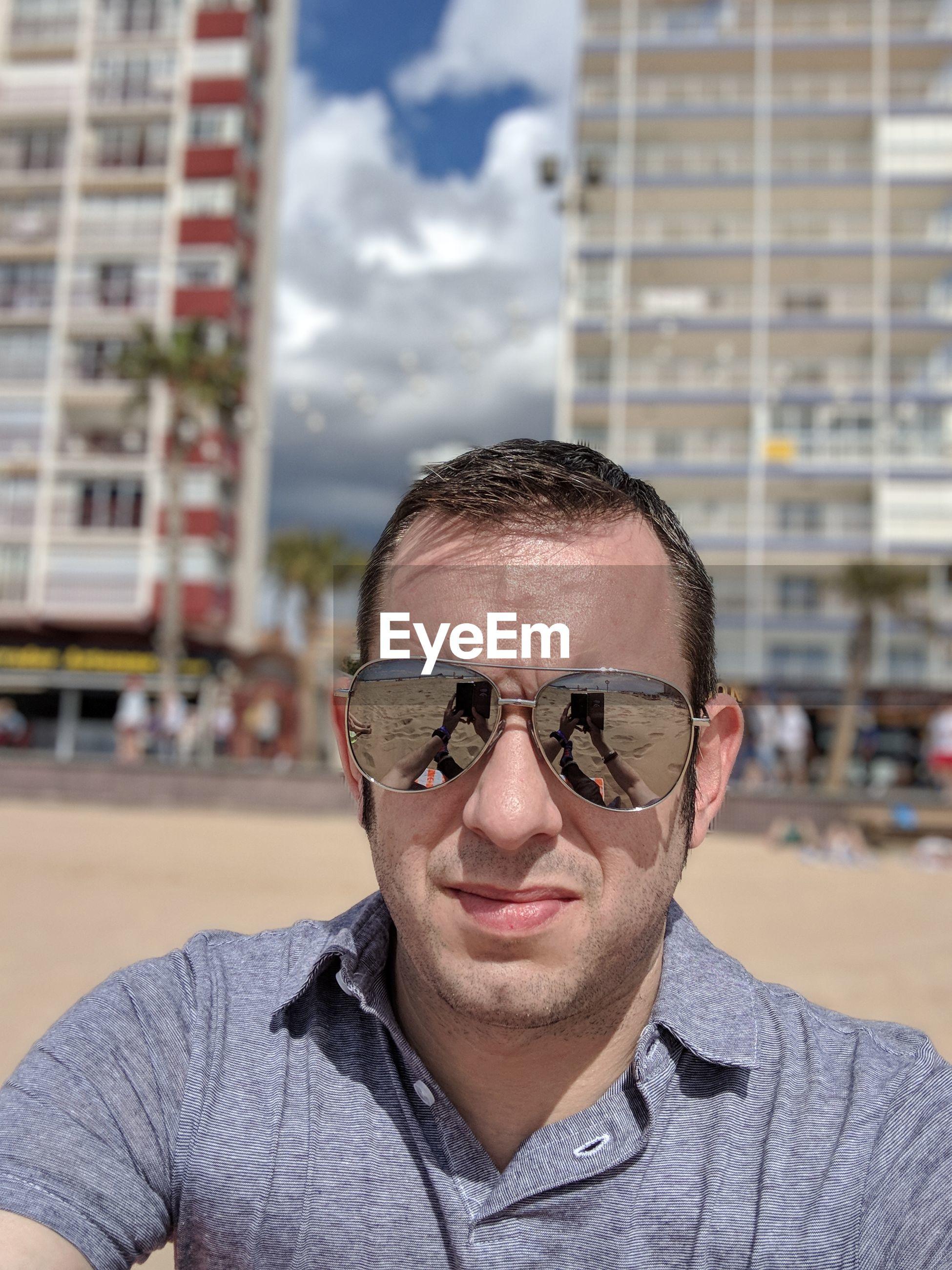 Portrait of man wearing sunglasses at beach