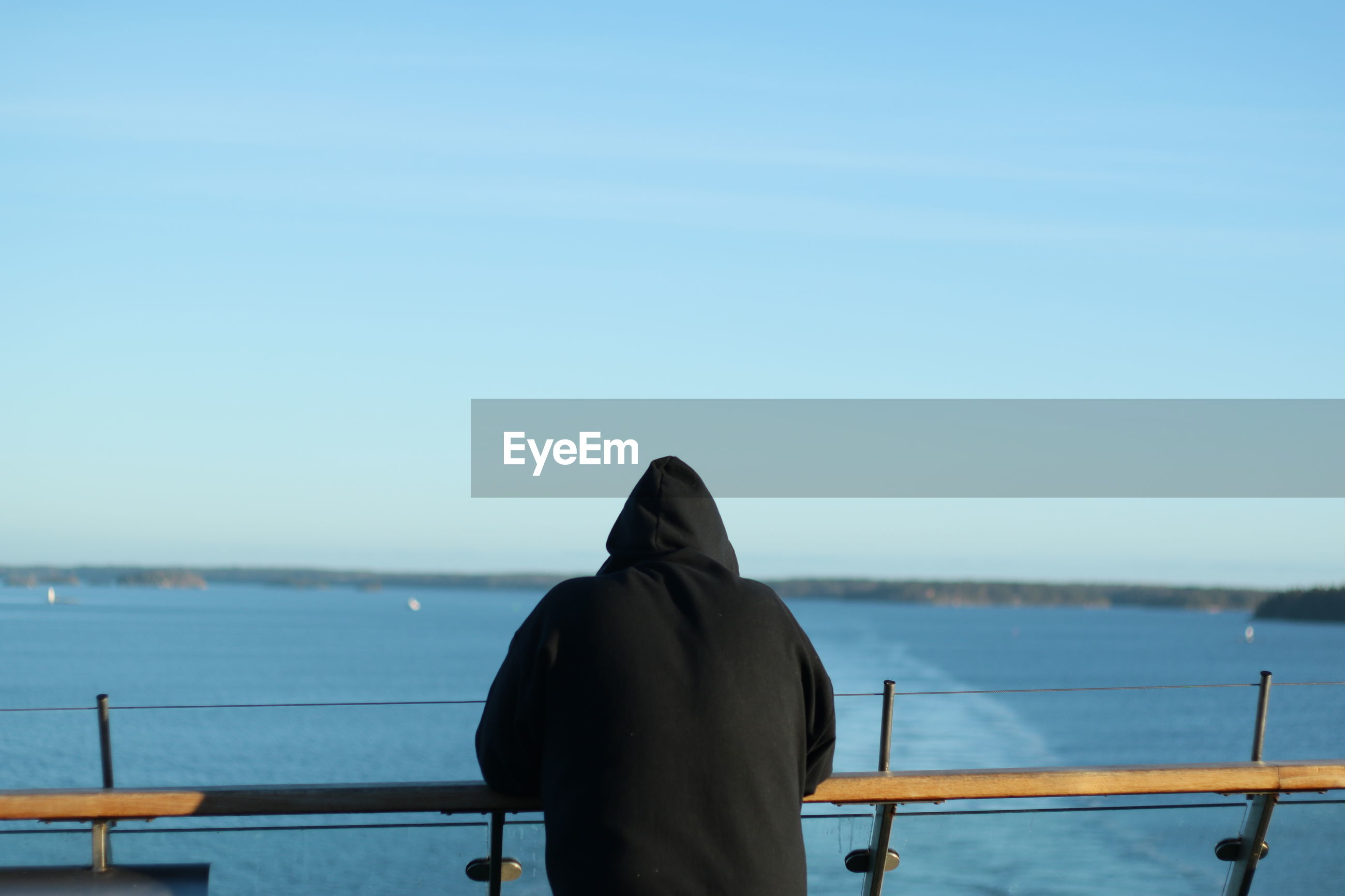 Rear view of man in sea against clear sky