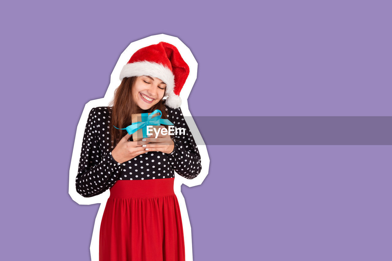 Smiling young woman wearing santa hat holding christmas present against purple background