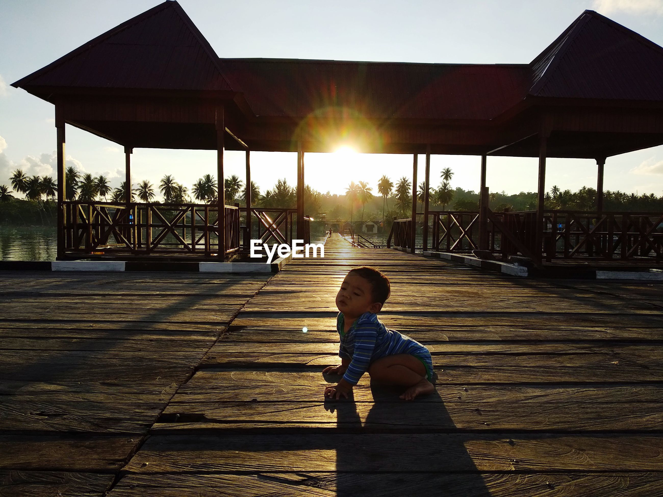 Side view of cute baby boy sitting on pier against sky during sunset