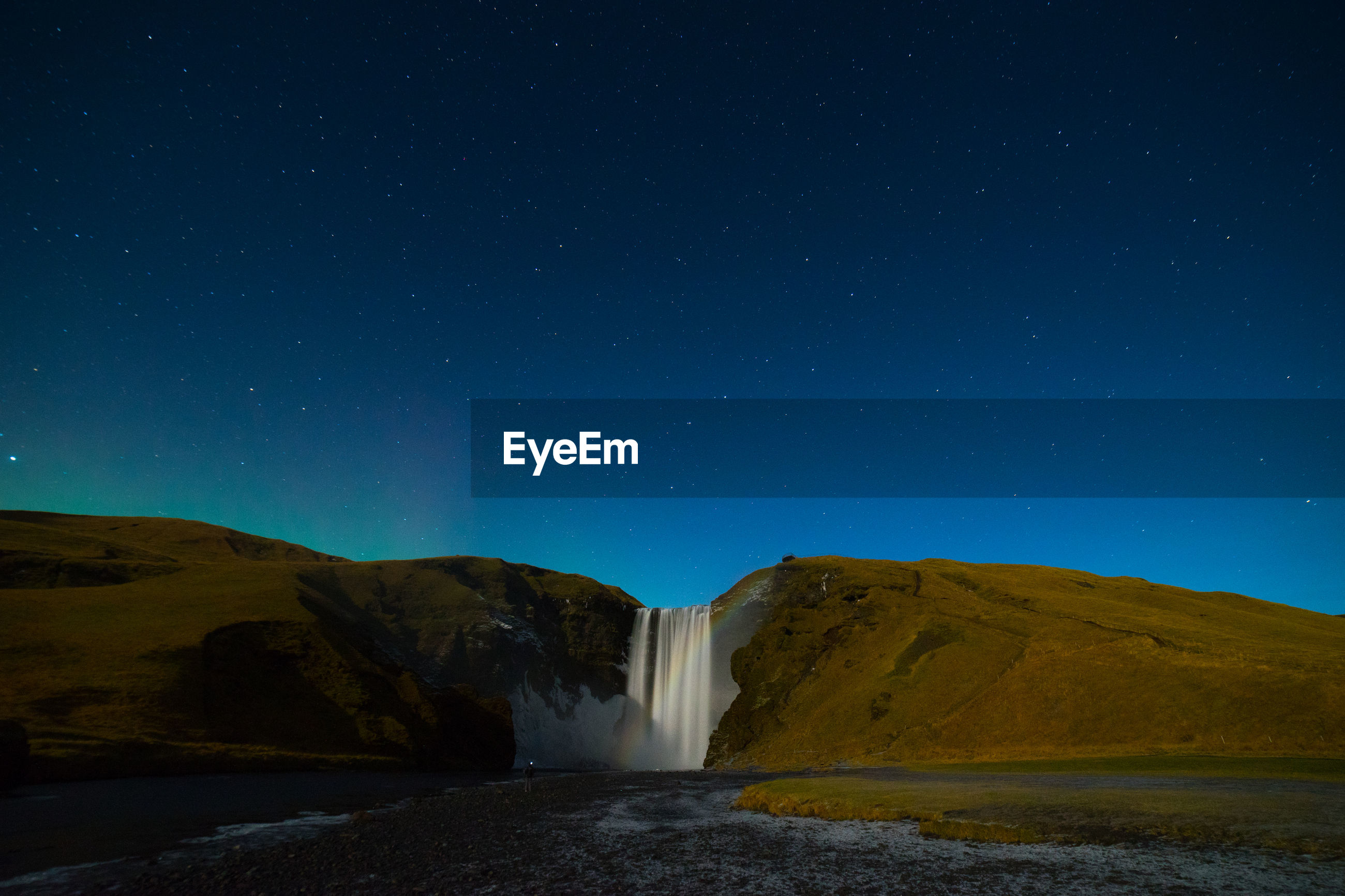 Scenic view of waterfall against clear sky at night