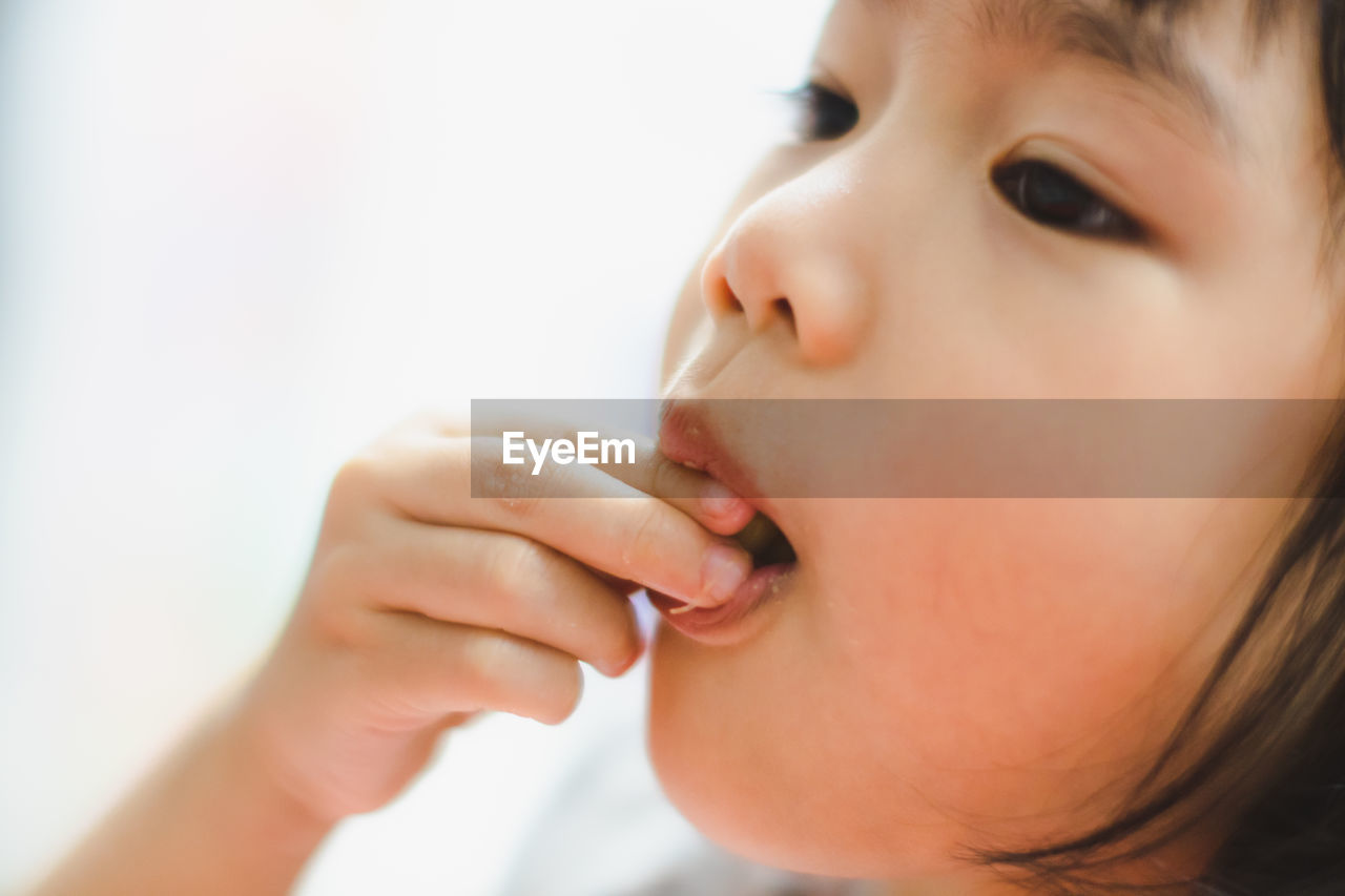 Close-Up Of Girl Eating Food Against White Background