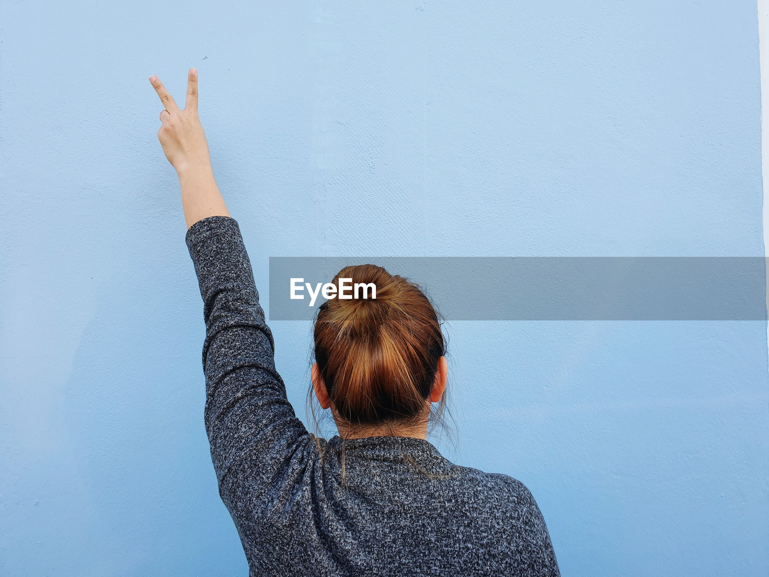 Rear view of woman making peace sign against wall