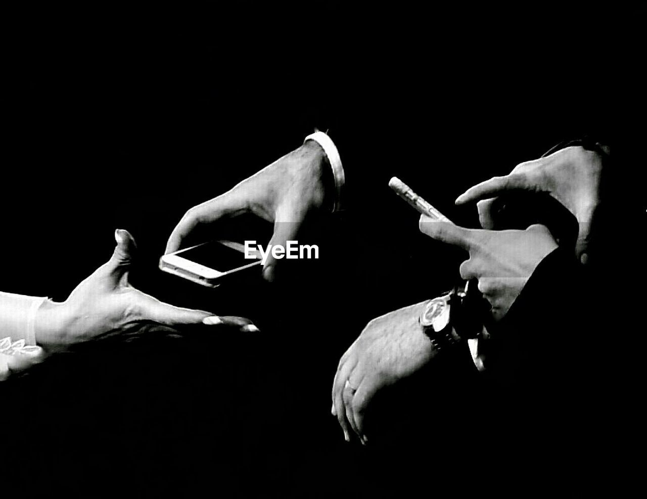 human hand, hand, black background, studio shot, human body part, indoors, men, people, holding, real people, body part, copy space, two people, human finger, lifestyles, finger, communication, adult, unrecognizable person