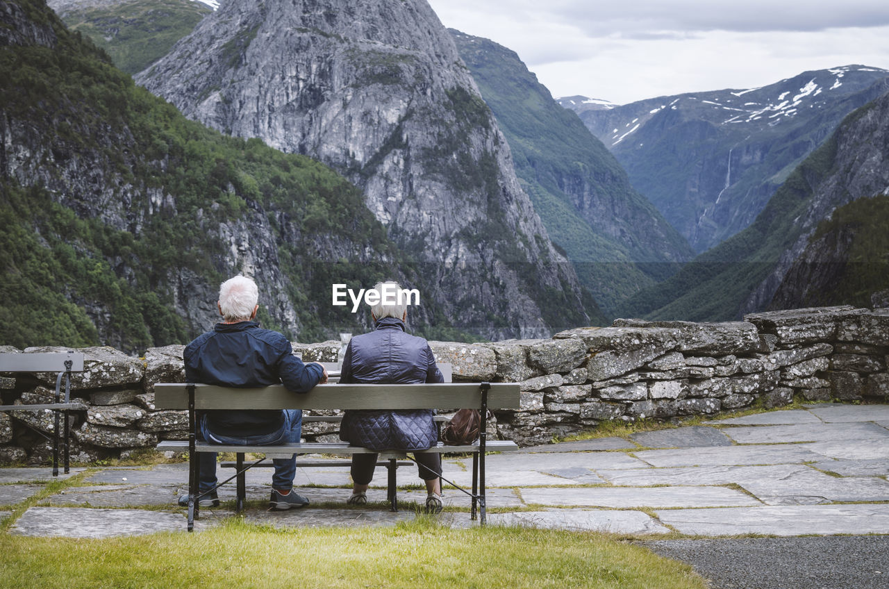 Rear View Of Couple Sitting On Bench Against Mountains