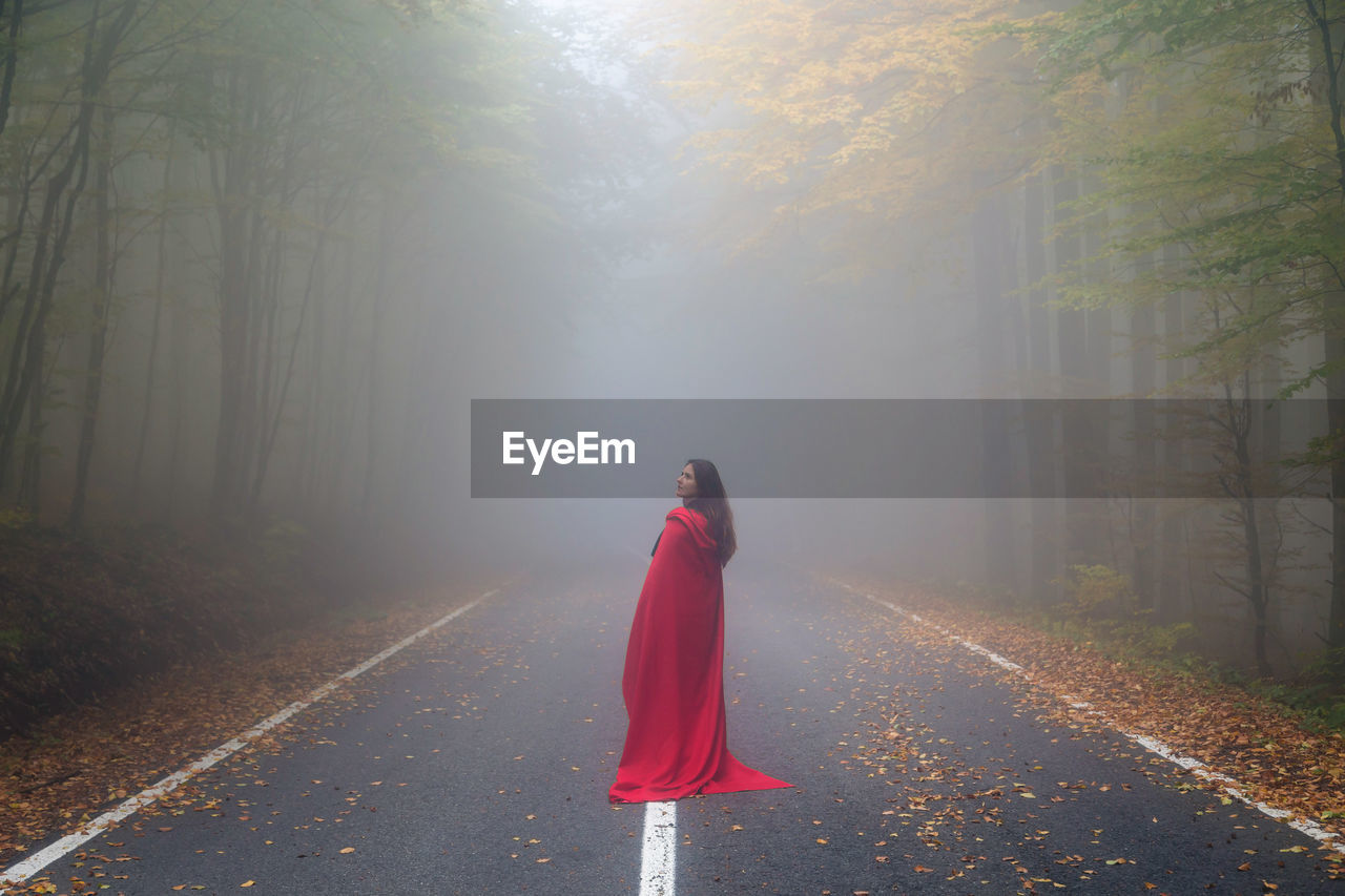 Rear View Of Woman Standing On Road In Forest During Foggy Weather