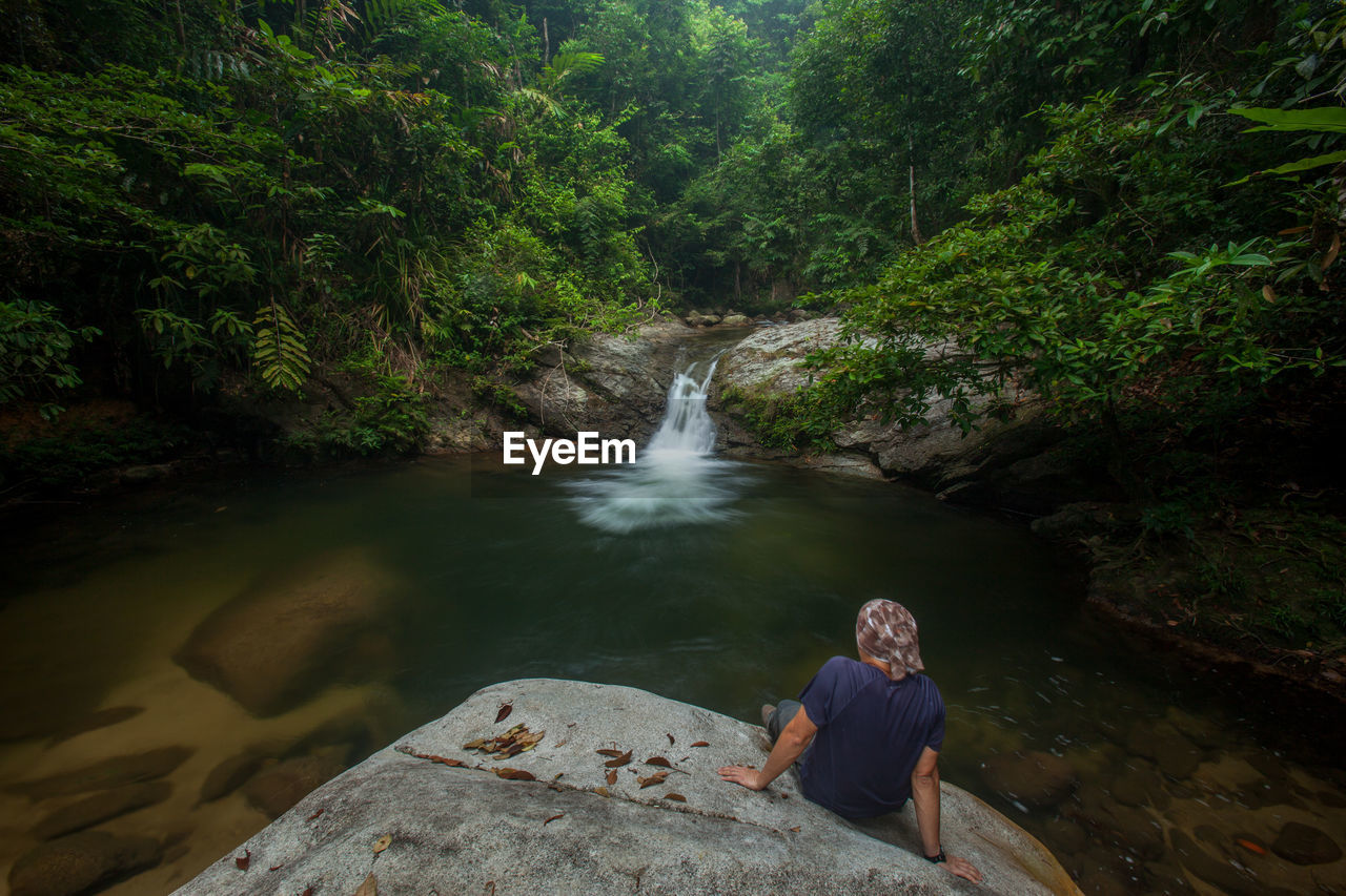 Person Sitting On Rock Looking At Stream Flowing Through Rocks In Forest
