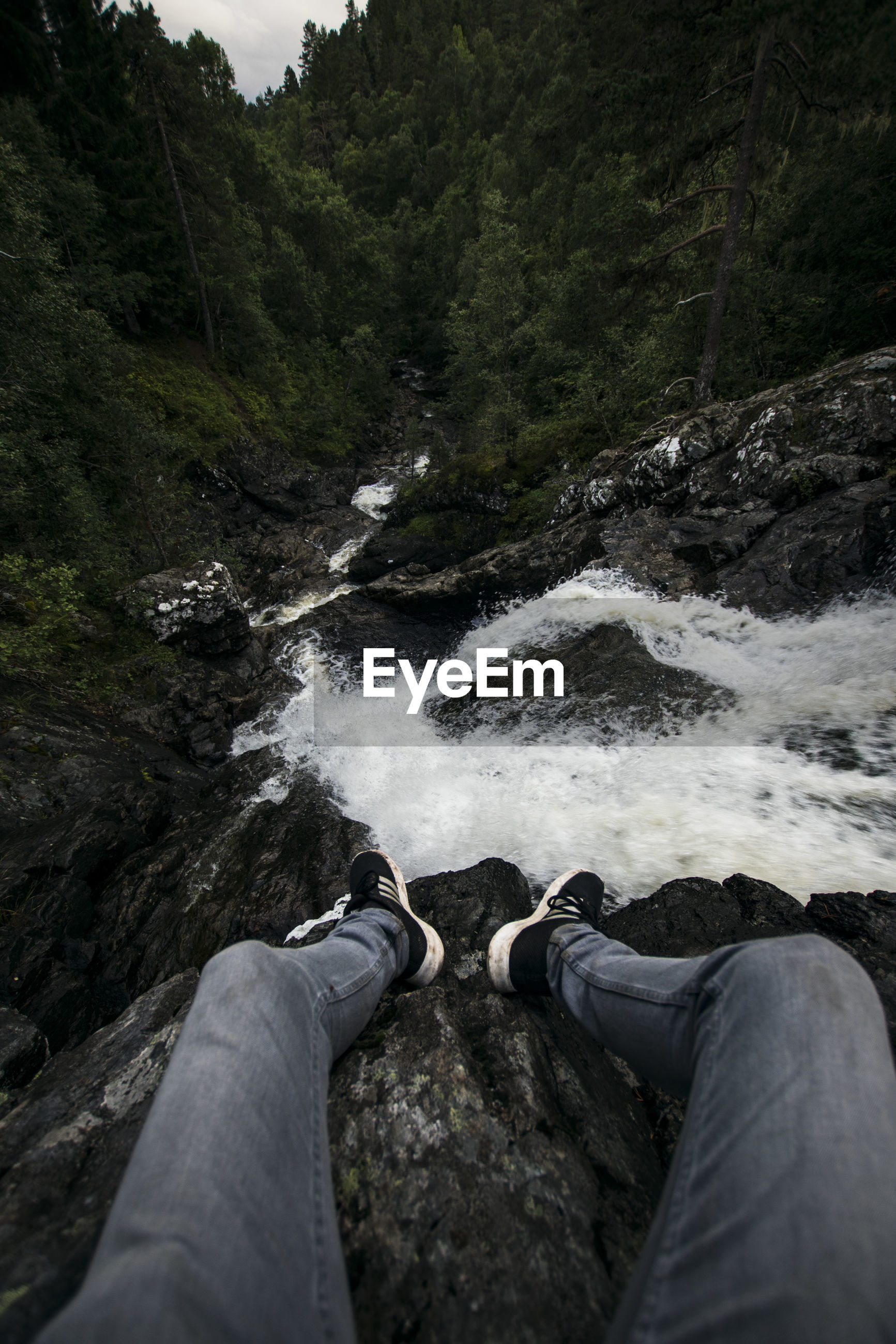 LOW SECTION OF PERSON BY WATERFALL IN PARK