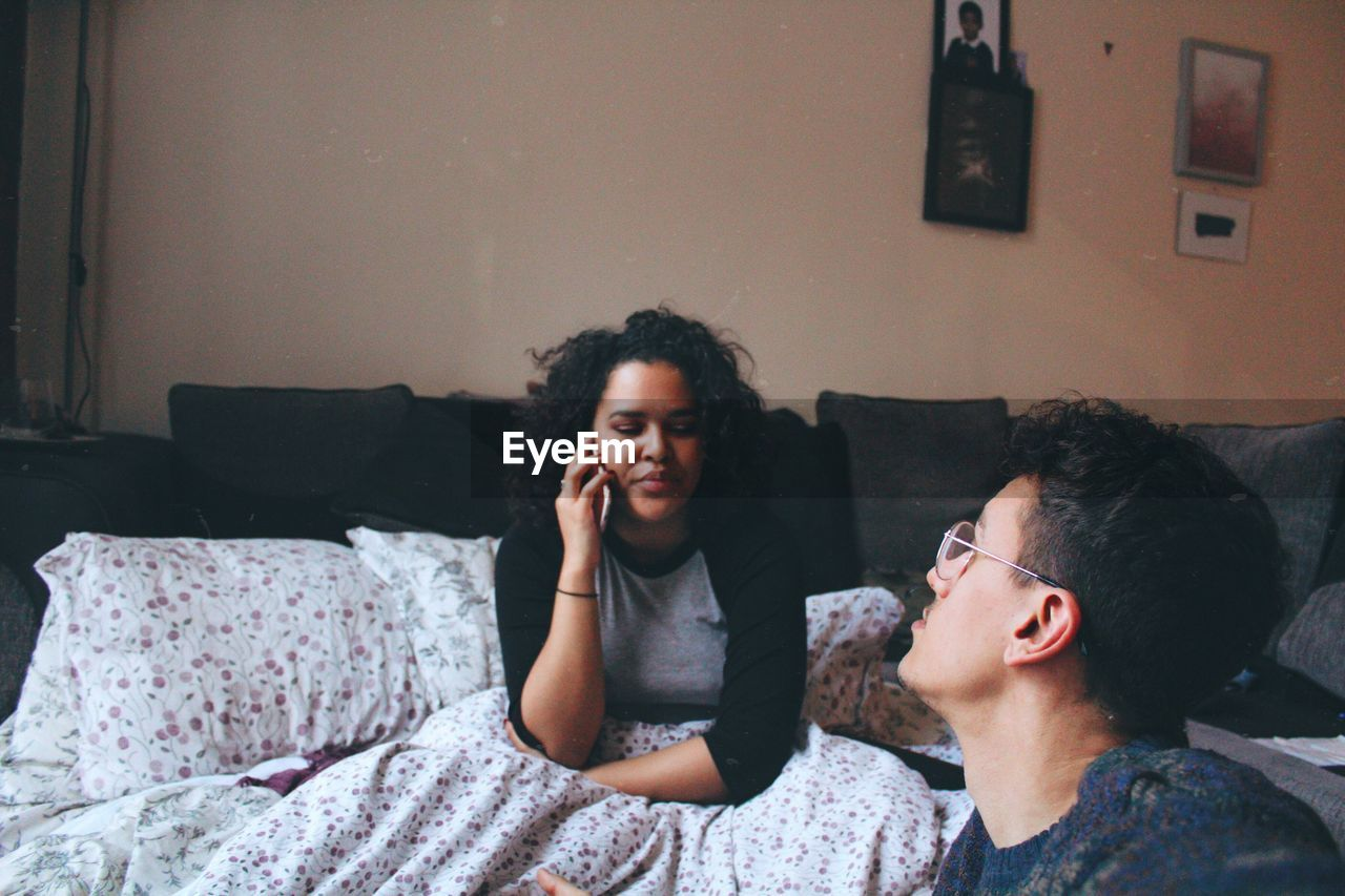 Young man looking at woman talking on smart phone while sitting on bed at home