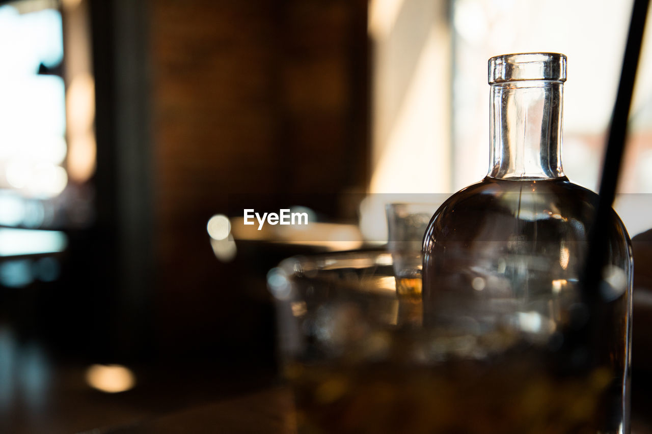 glass - material, food and drink, drink, refreshment, transparent, indoors, container, bottle, glass, no people, alcohol, close-up, table, household equipment, bar - drink establishment, drinking glass, still life, selective focus, focus on foreground, wine bottle, bar counter