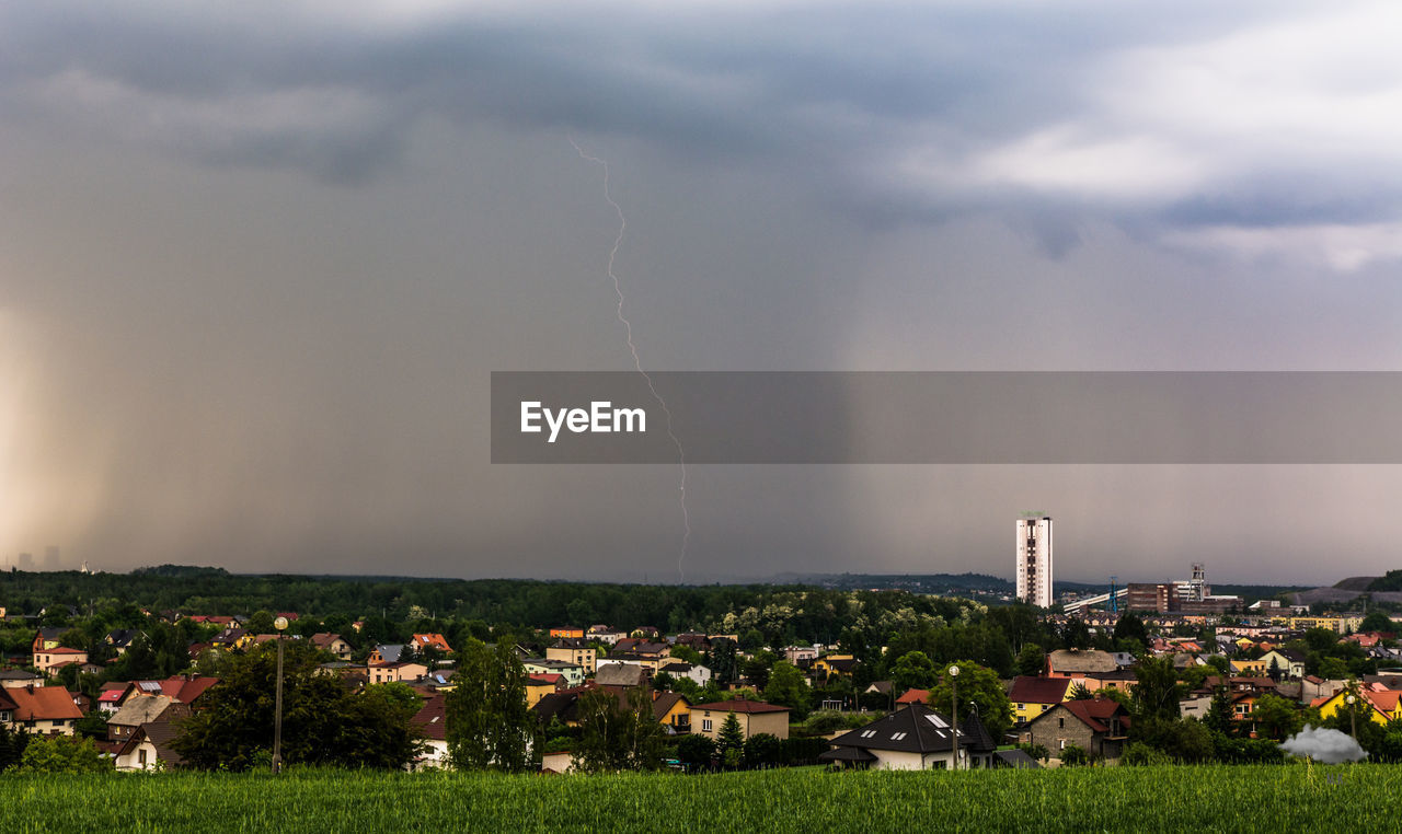 cloud - sky, building exterior, architecture, sky, built structure, storm, city, building, lightning, nature, power in nature, residential district, environment, thunderstorm, storm cloud, no people, house, power, overcast, outdoors, townscape, cityscape, ominous, pollution