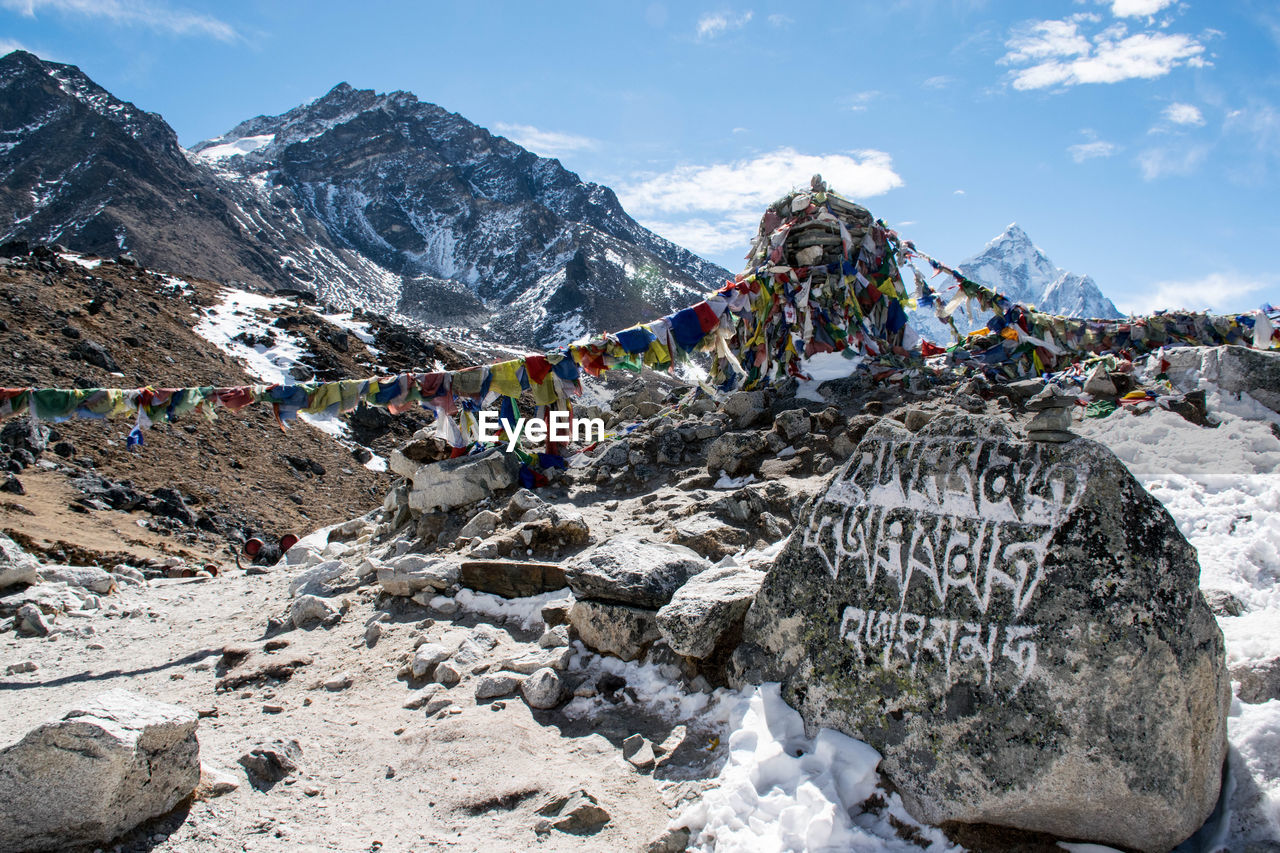 Text On Rock By Prayer Flags On Mountain During Winter