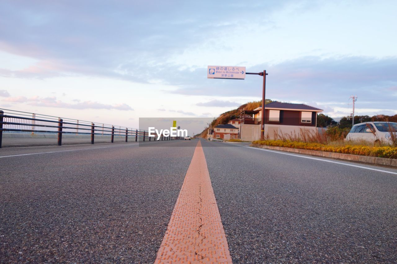 sign, sky, cloud - sky, transportation, road, direction, architecture, the way forward, built structure, symbol, nature, road marking, marking, communication, building exterior, diminishing perspective, vanishing point, no people, day, empty, surface level, outdoors, dividing line, long
