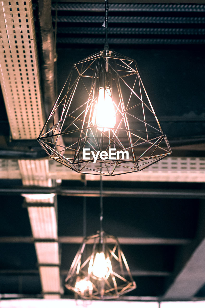illuminated, lighting equipment, hanging, electricity, light, low angle view, indoors, no people, electric light, night, glowing, close-up, electric lamp, pendant light, ceiling, decoration, focus on foreground, home interior, technology, metal, electrical equipment