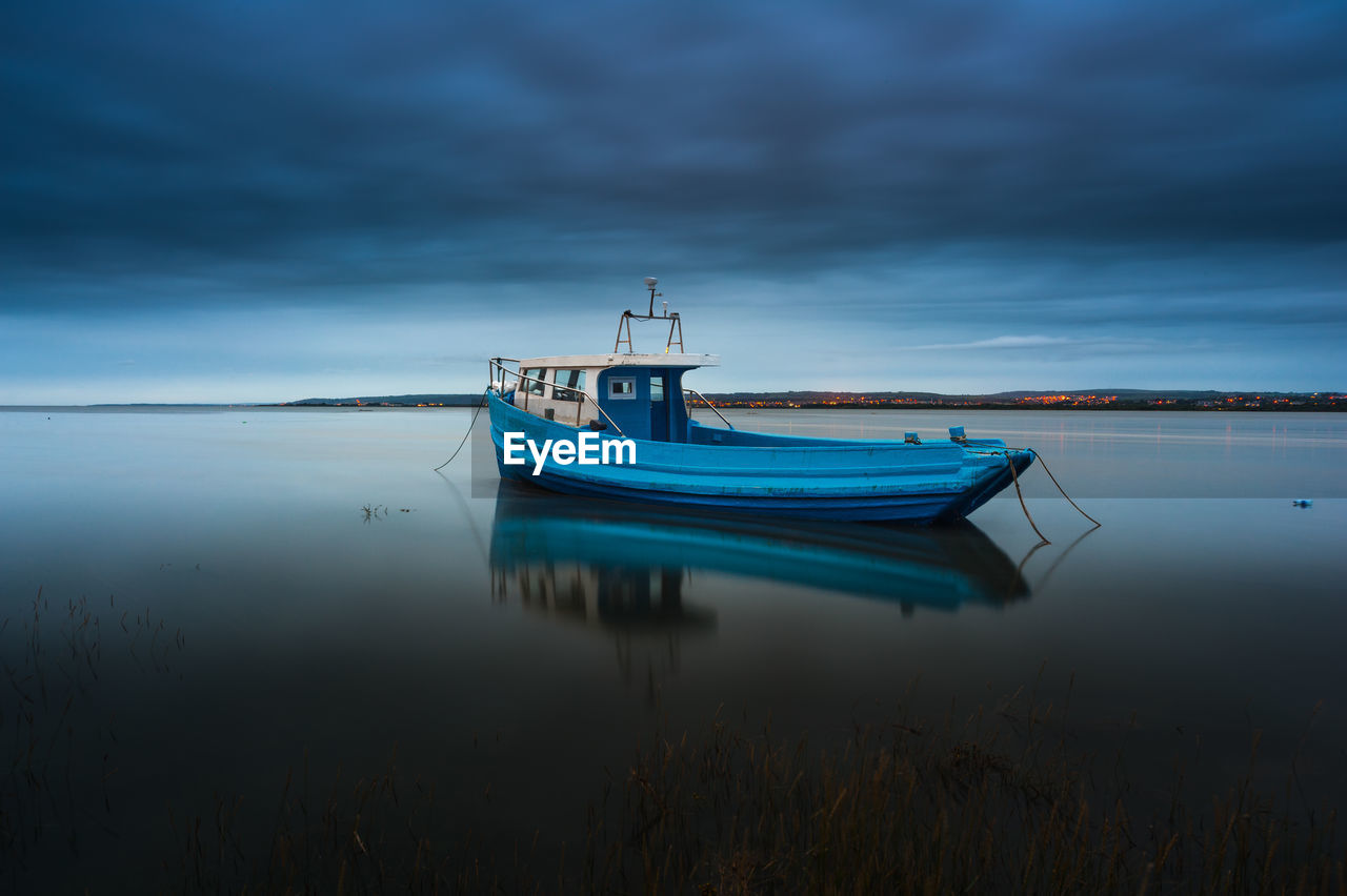 Boat Moored In Sea Against Sky At Dusk