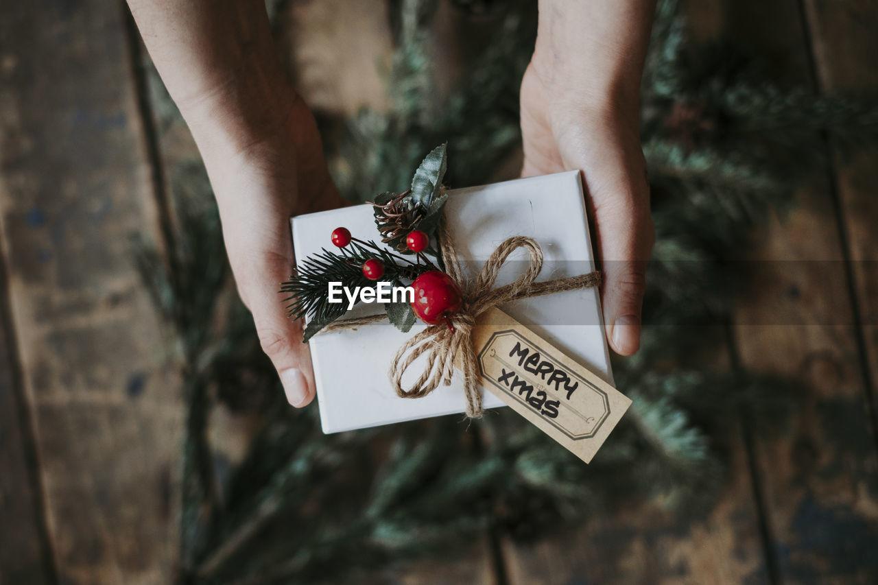 Cropped hands holding christmas present over hardwood floor