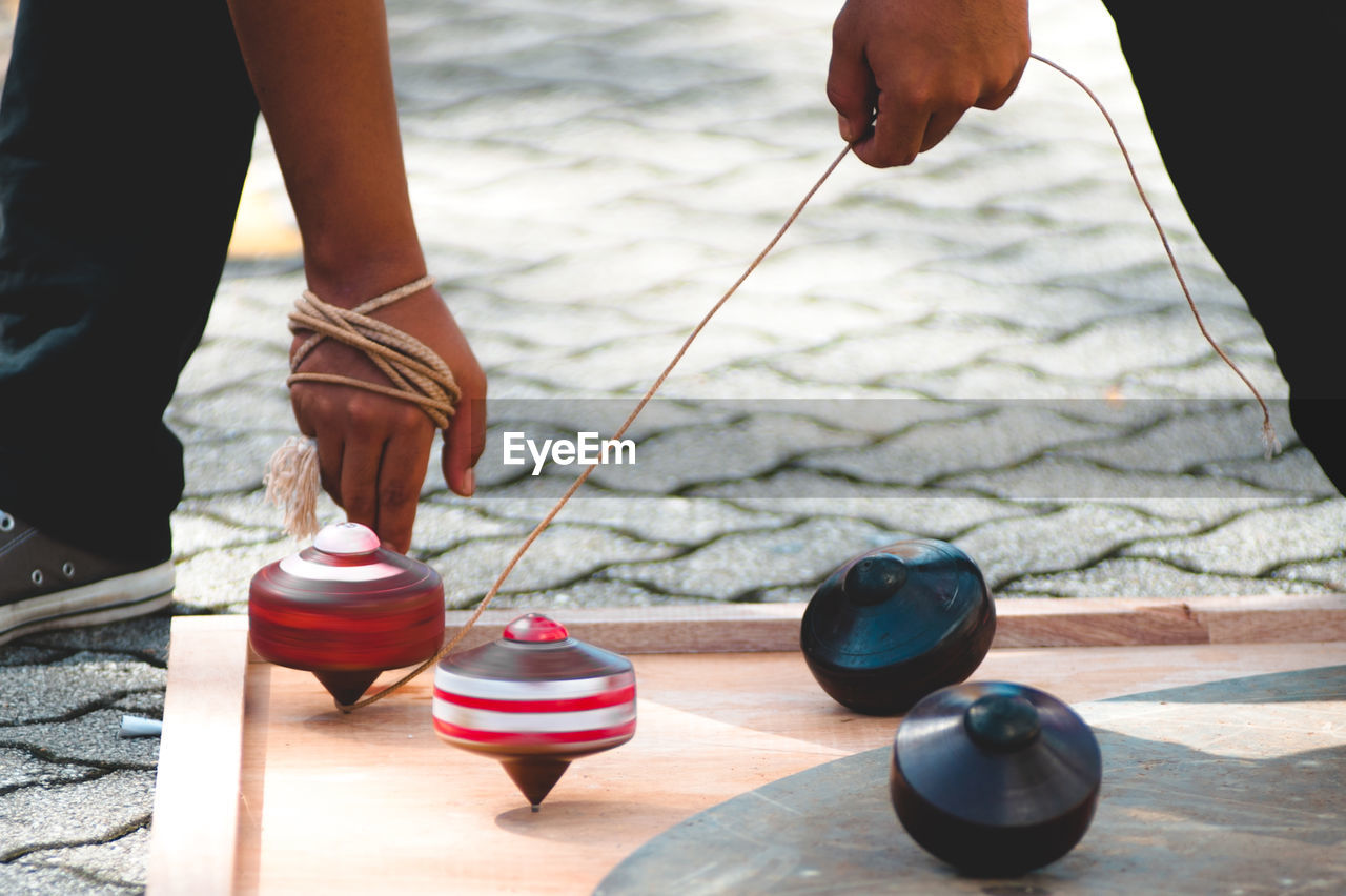 Low section of man playing with spinning top on wooden board over footpath